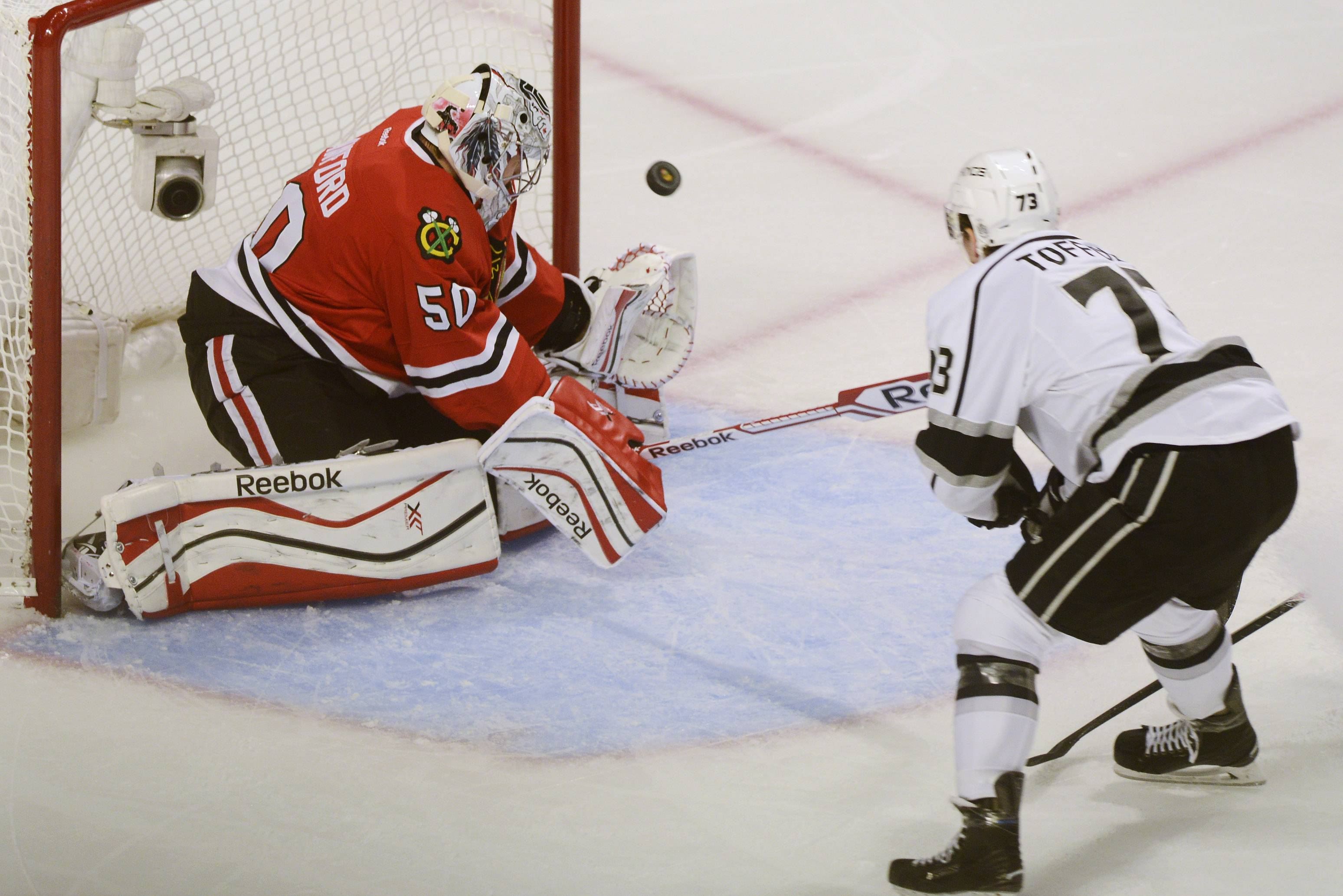 The puck gets past Chicago Blackhawks goalie Corey Crawford for a second-period goal as Los Angeles Kings center Tyler Toffoli skates toward the net during Sunday's game at the United Center in Chicago.