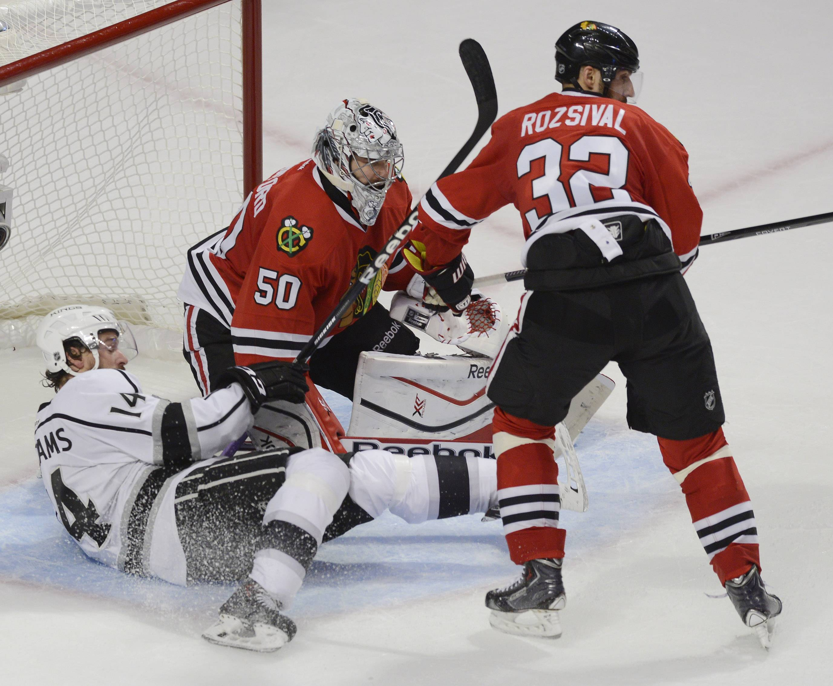 Los Angeles Kings right wing Justin Williams, left, falls as Chicago Blackhawks goalie Corey Crawford and defenseman Michal Rozsival protect the net during Sunday's game at the United Center in Chicago.