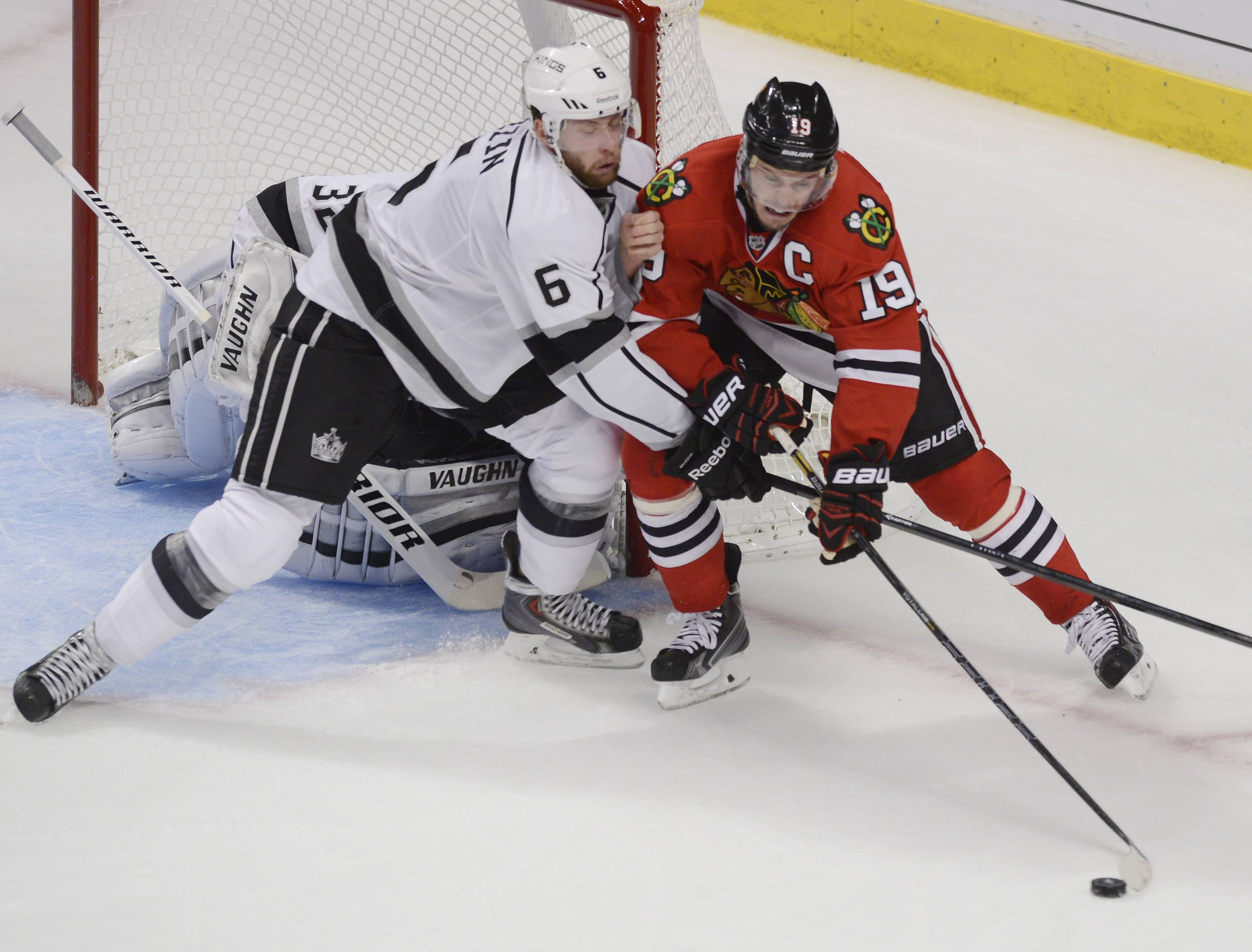 Chicago Blackhawks center Jonathan Toews, right, gets hit in front of the net by Los Angeles Kings defenseman Jake Muzzin during Sunday's game at the United Center in Chicago.