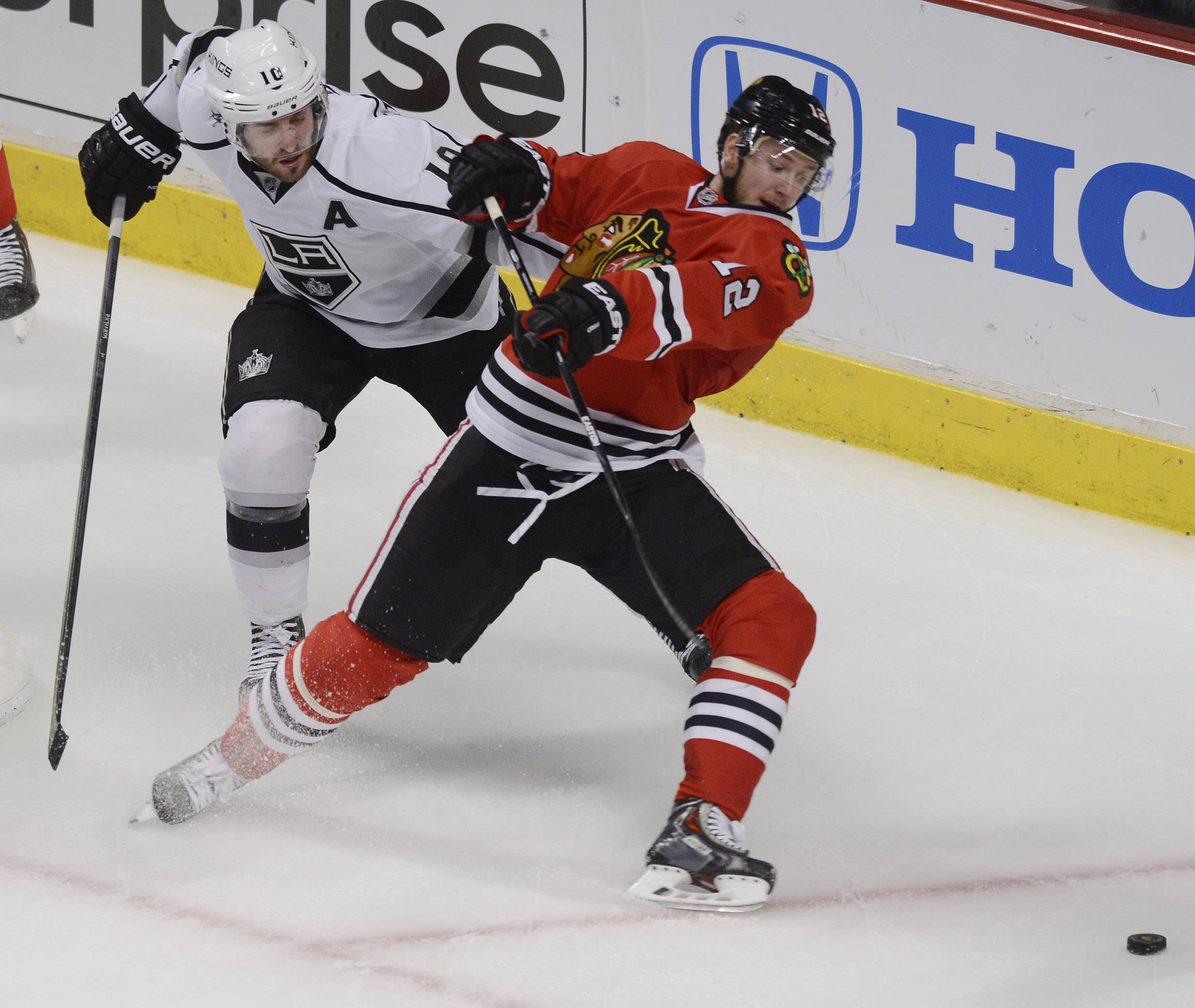 Chicago Blackhawks center Peter Regin, right, and Los Angeles Kings center Mike Richards make contact during Sunday's game at the United Center in Chicago.