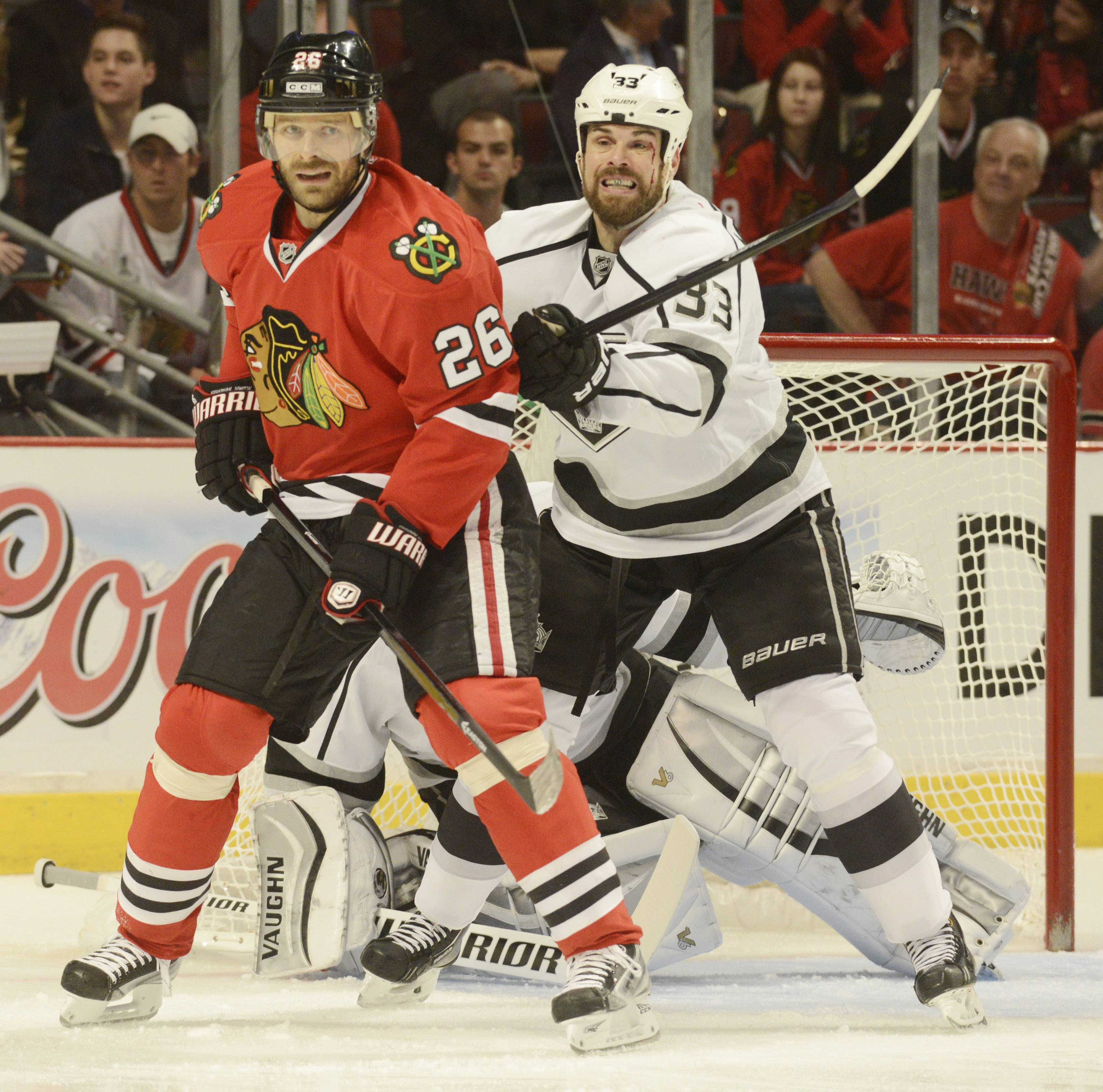 Los Angeles Kings defenseman Willie Mitchell, right, tries to push Chicago Blackhawks center Michal Handzus away from the net during Sunday's game at the United Center in Chicago.