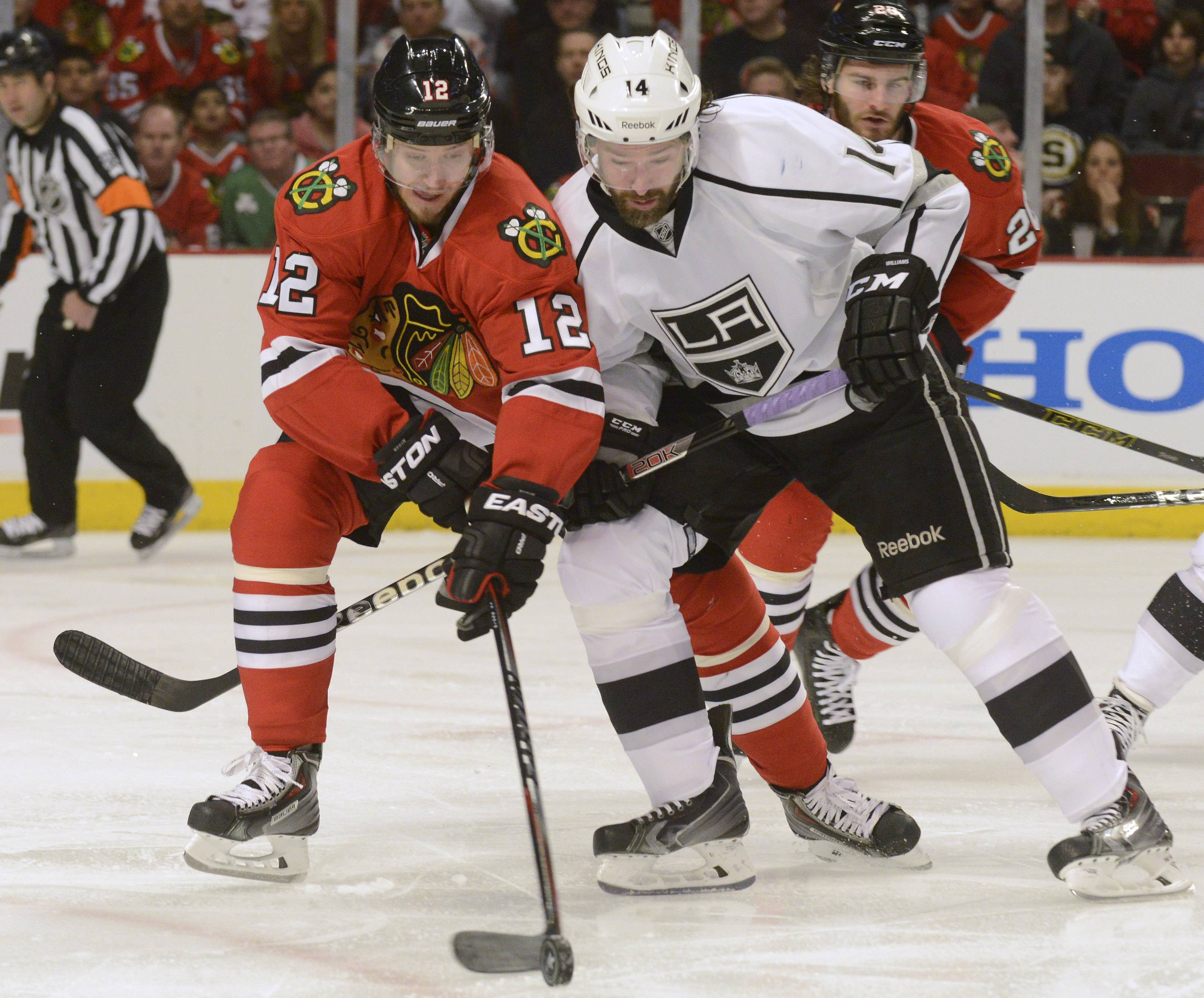 Chicago Blackhawks center Peter Regin, left, tries to take the puck from Los Angeles Kings right wing Justin Williams during Sunday's game at the United Center in Chicago.