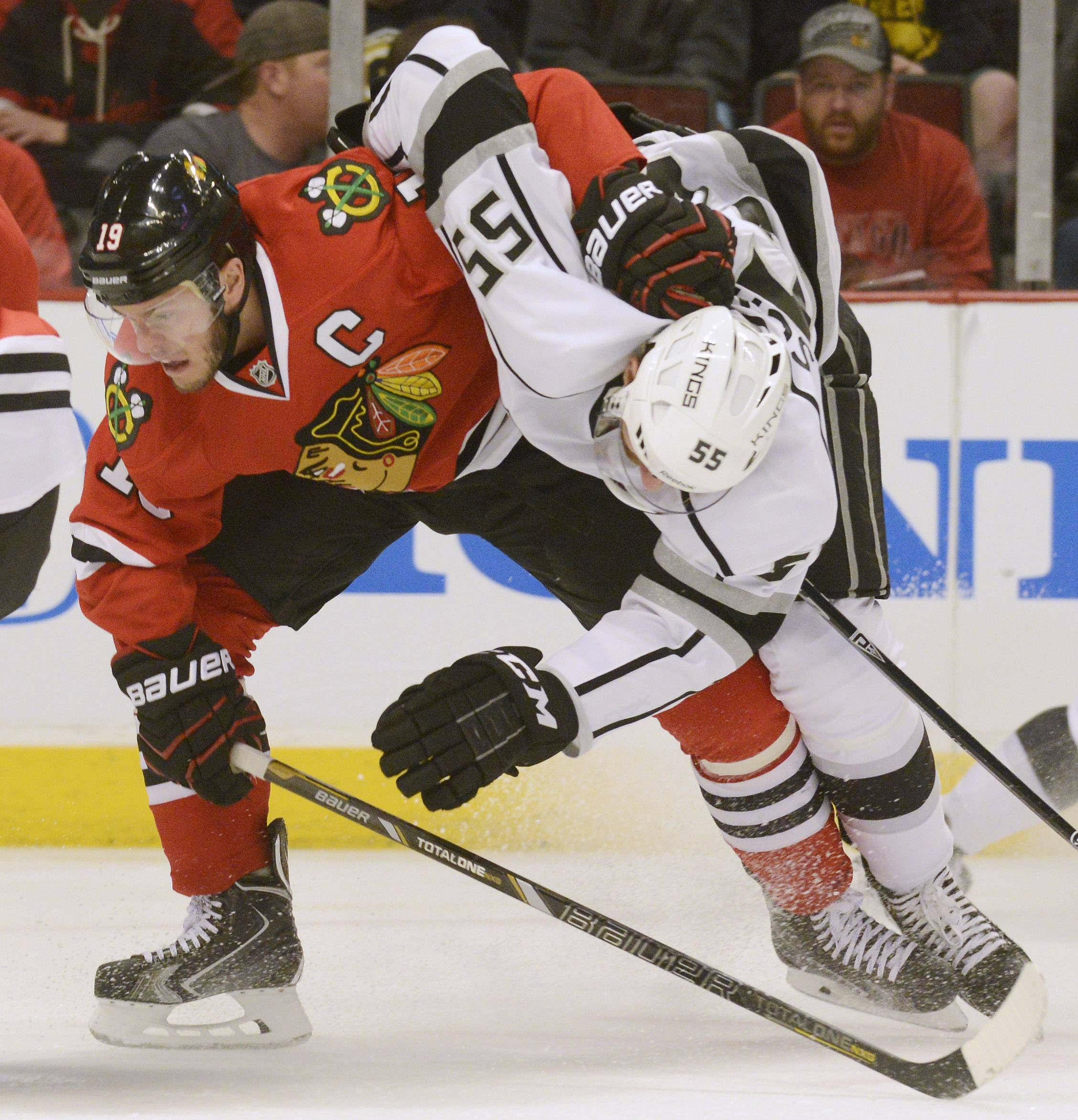 Chicago Blackhawks center Jonathan Toews, left, and Los Angeles Kings defenseman Jeff Schultz take one another down to the ice on a play during Sunday's game at the United Center in Chicago.