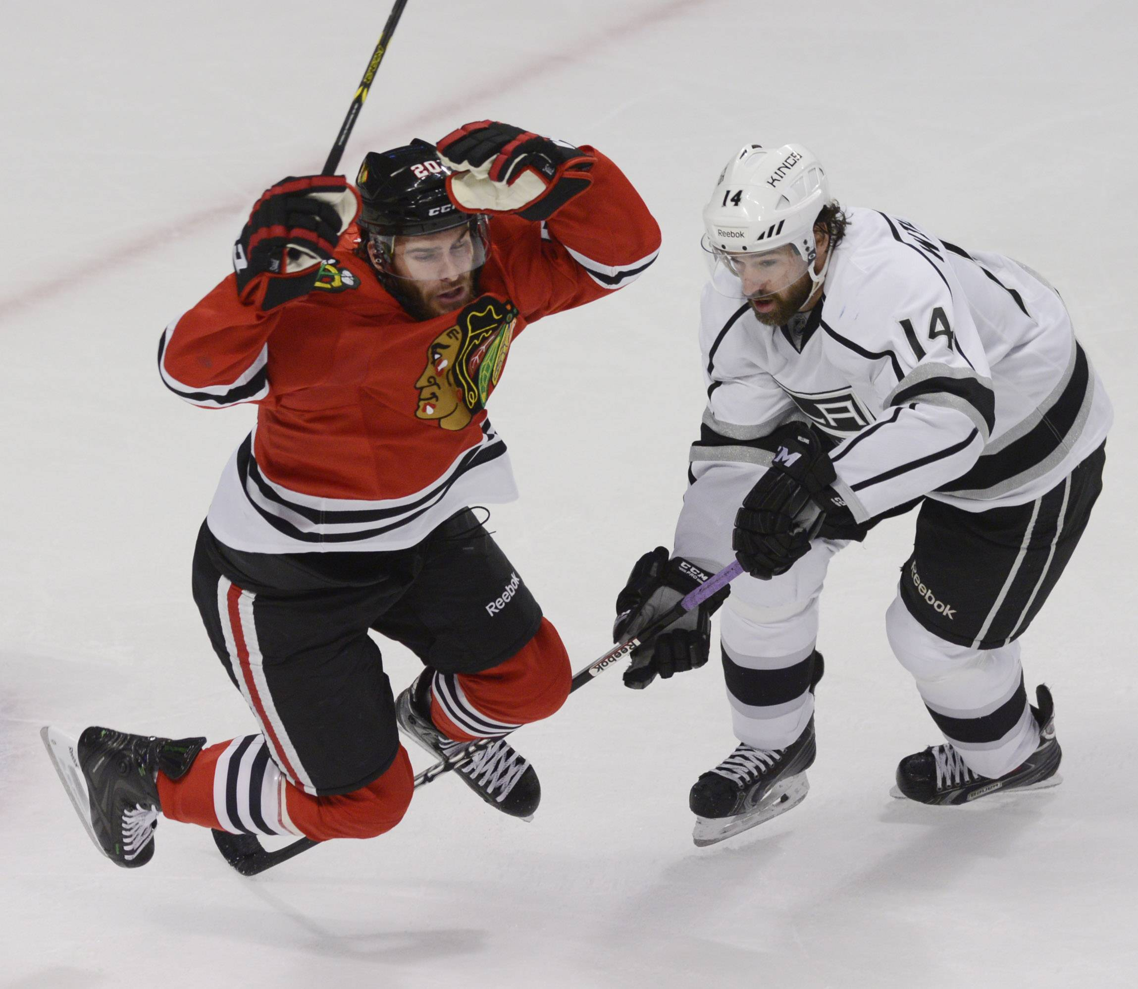 Chicago Blackhawks left wing Brandon Saad trips over Los Angeles Kings right wing Justin Williams' stick during Sunday's game at the United Center in Chicago.