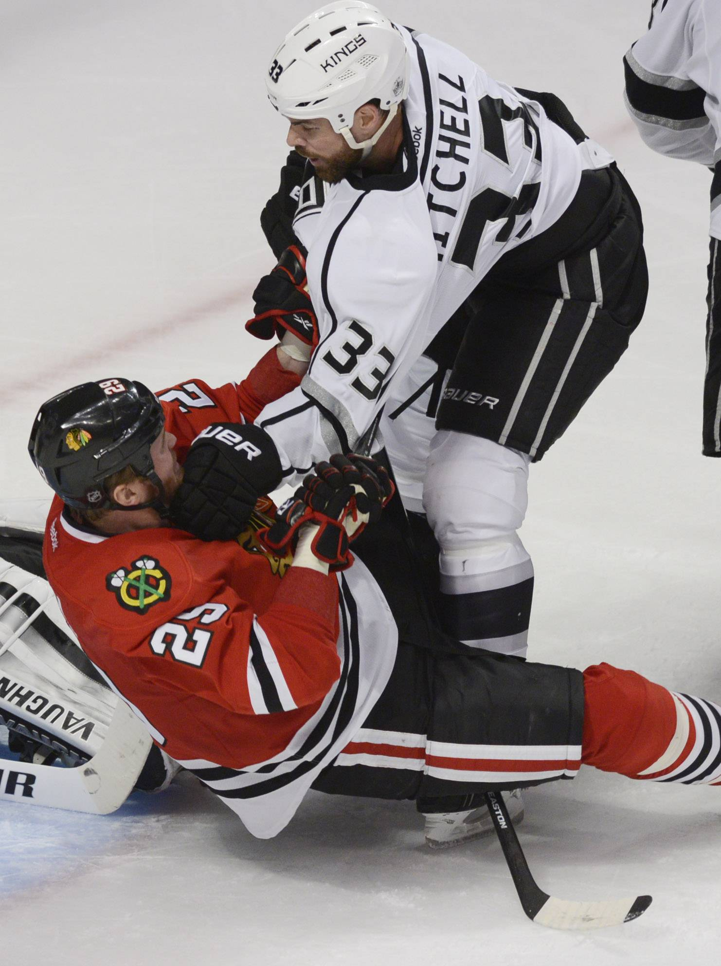 Los Angeles Kings defenseman Willie Mitchell knocks Chicago Blackhawks left wing Bryan Bickell to the ice in front of the Kings' goal during Sunday's game at the United Center in Chicago.