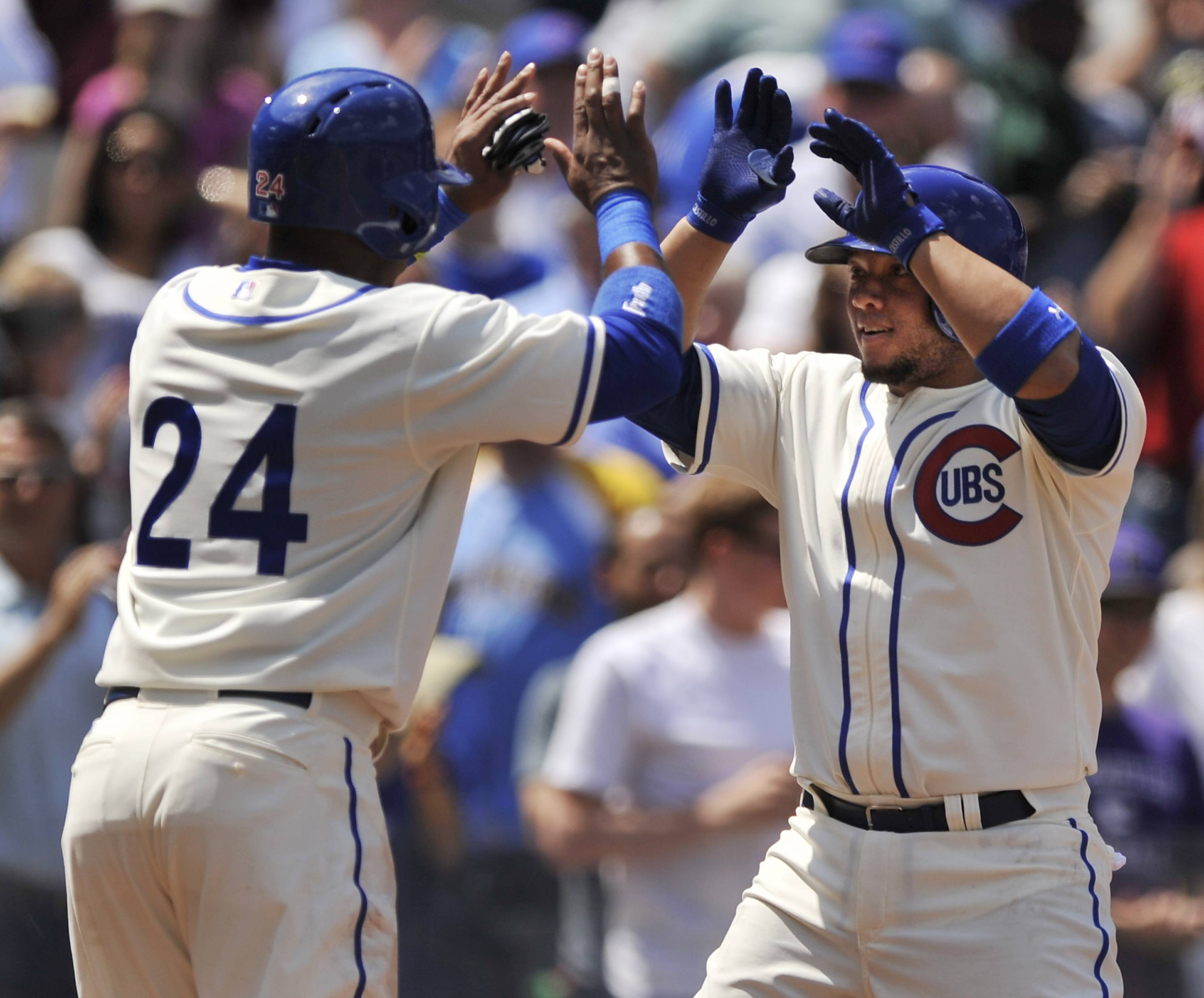 Chicago Cubs' Welington Castillo right, celebrates with teammate Luis Valbuena (24) at home plate after hitting a two-run homer during the second inning of a baseball game against the Milwaukee Brewers in Chicago, Sunday, May 18, 2014.