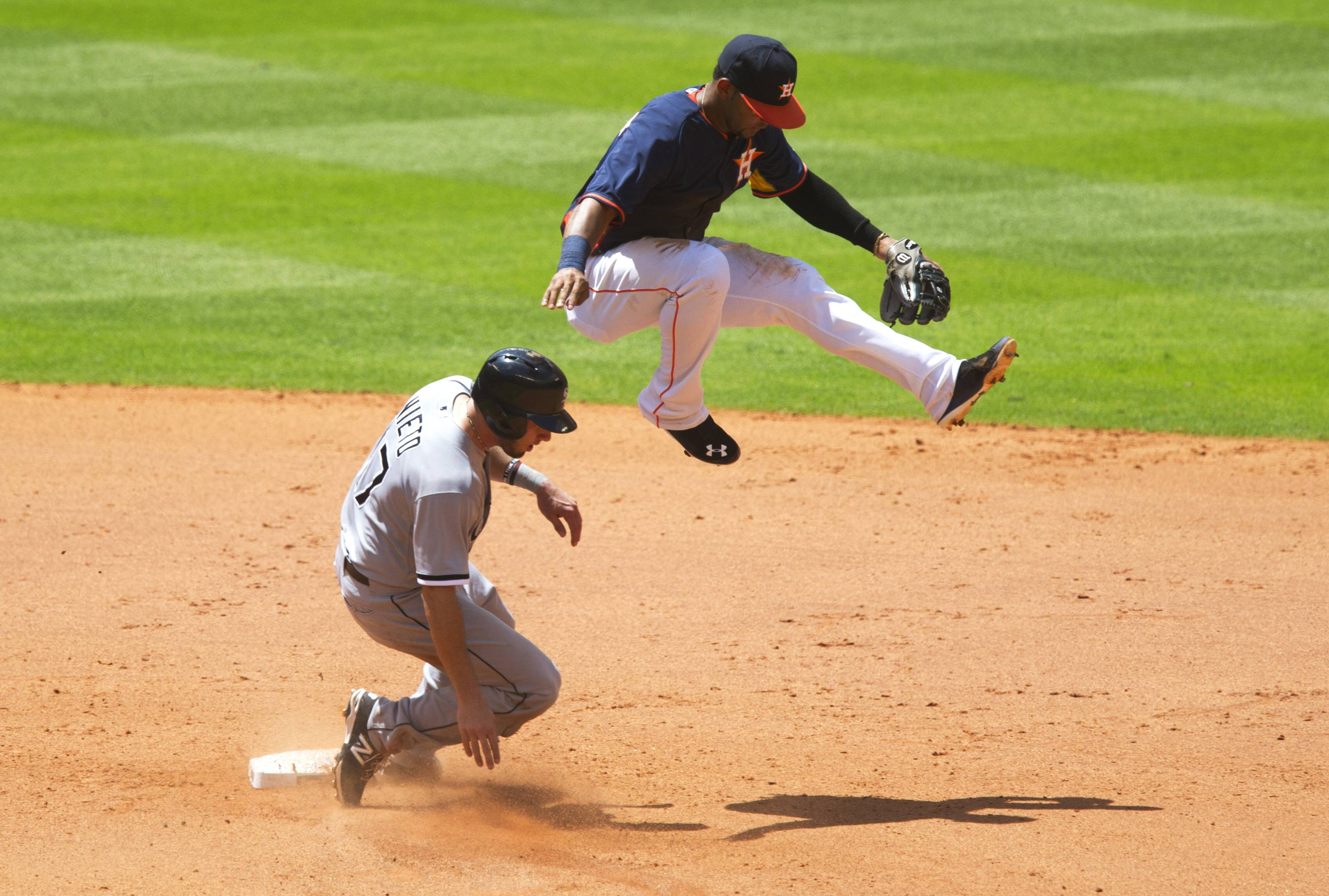 Houston Astros shortstop Jonathan Villar, right, leaps over Chicago White Sox's Adrian Nieto after making an out at second in the fifth inning during a baseball game, Sunday, May 18, 2014, in Houston.