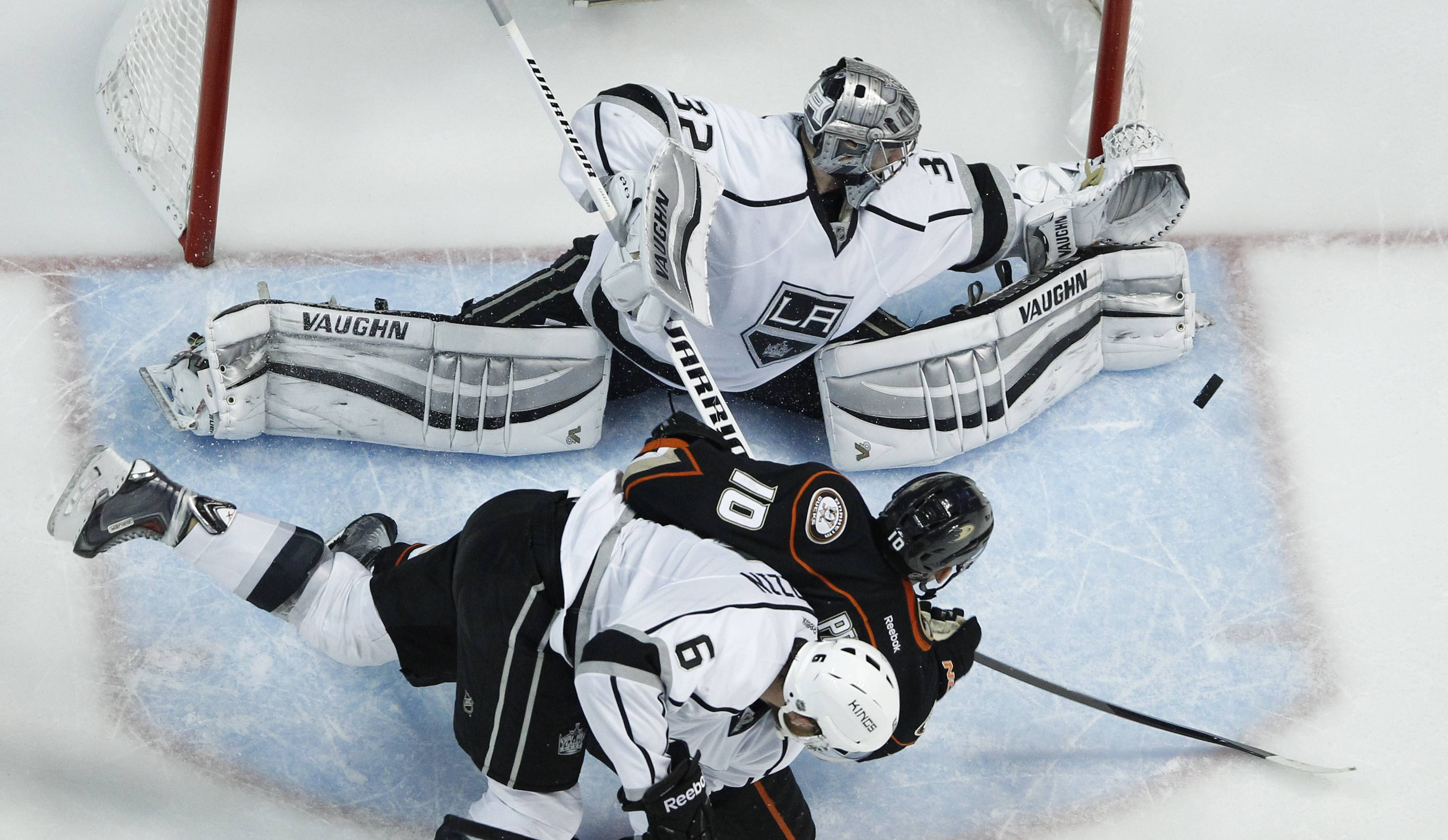 Los Angeles Kings goalie Jonathan Quick blocks a shot from Anaheim Ducks right wing Corey Perry with the help of Jake Muzzin during the second period in Game 7 of an NHL hockey second-round Stanley Cup playoff series in Anaheim, Calif., Friday, May 16, 2014.