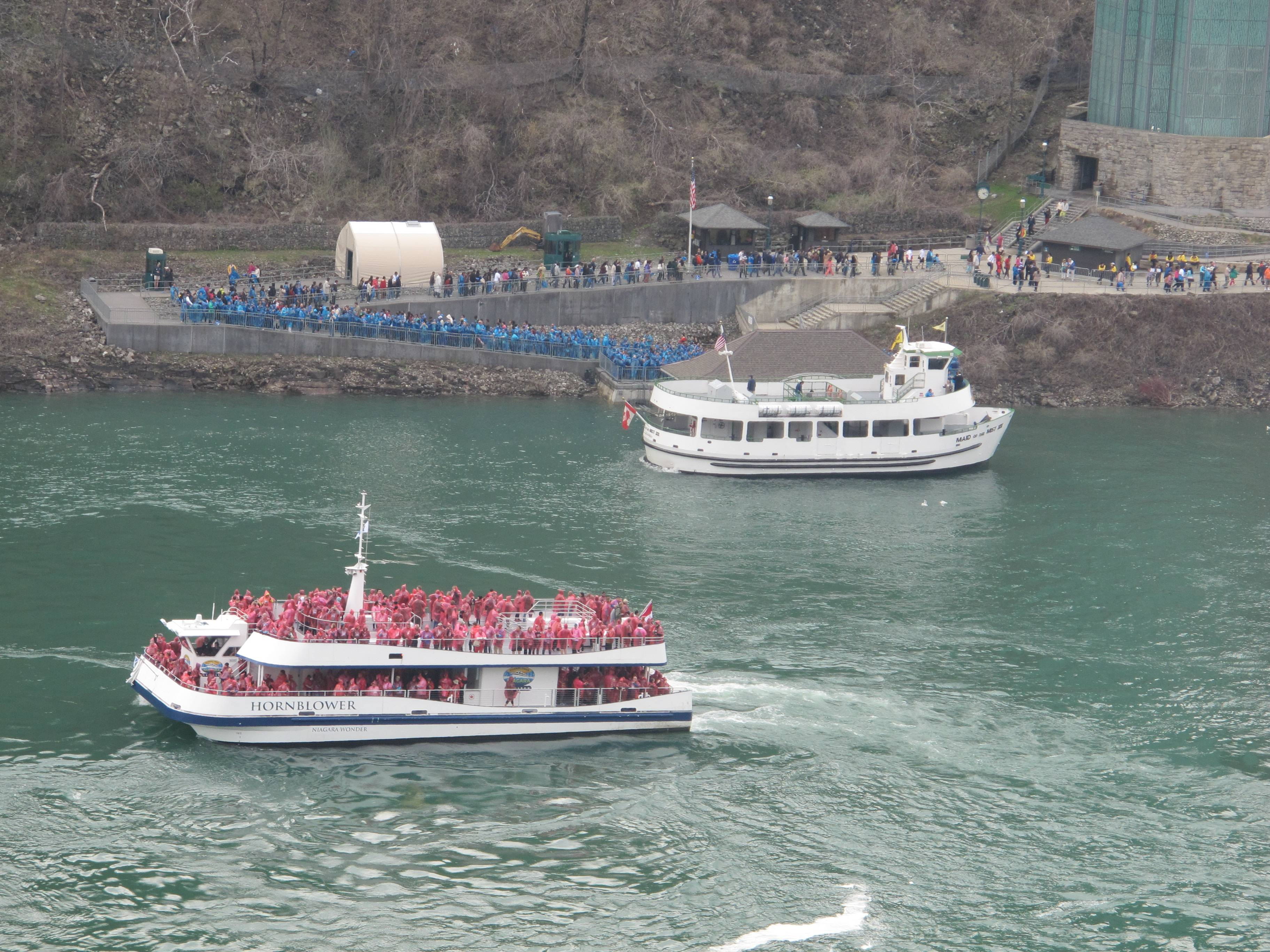 A Hornblower Niagara Cruises Catamaran, foreground, and a Maid of the Mist boat, background, in the Niagara Gorge below Niagara Falls.