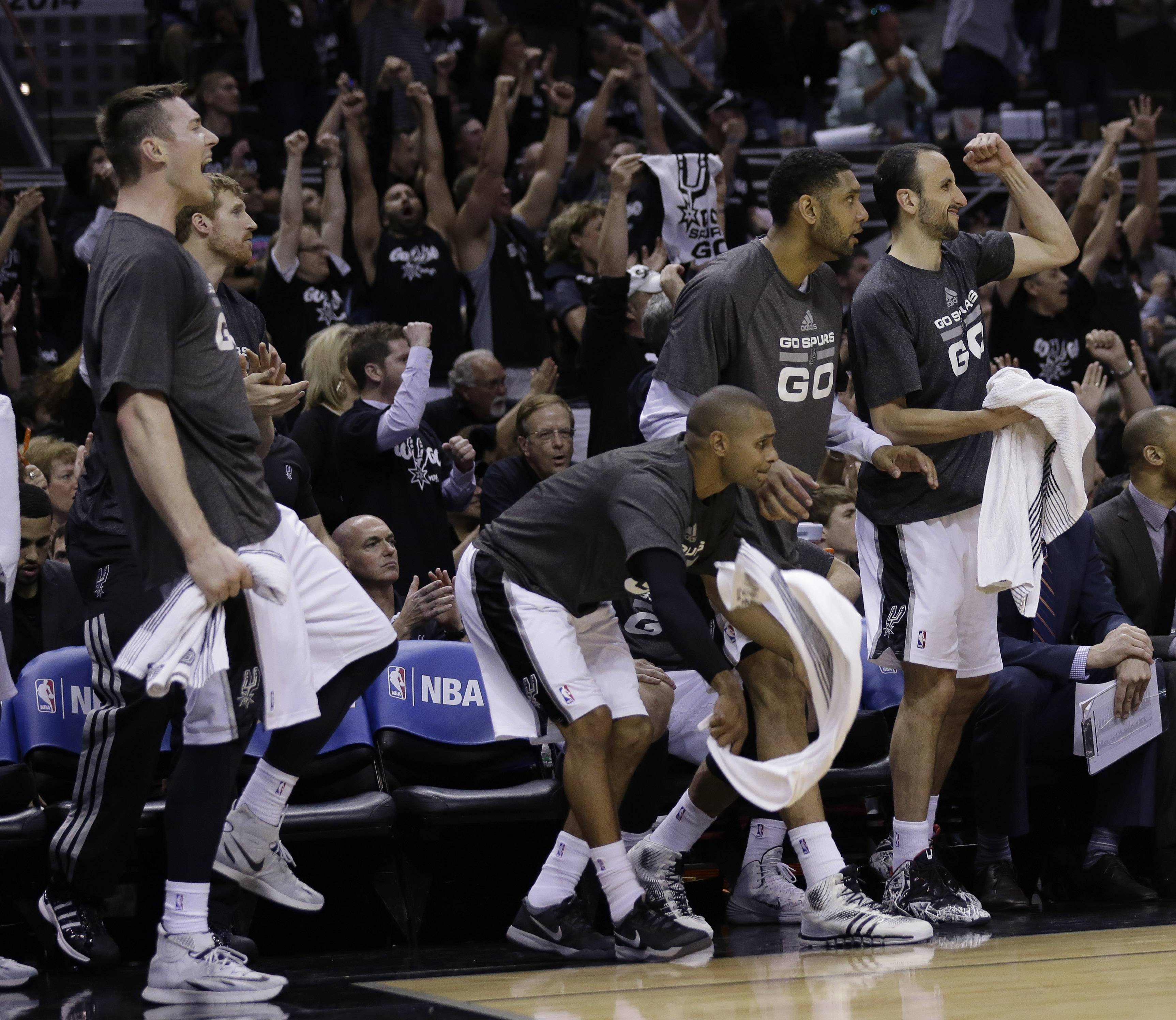 San Antonio Spurs player, from left, Aron Baynes, Patty Mills, Tim Duncan and Manu Ginobili, celebrate from the bench during the second half of Game 1 of a Western Conference finals NBA basketball playoff series Monday against the Oklahoma City Thunder in San Antonio. San Antonio won 122-105.