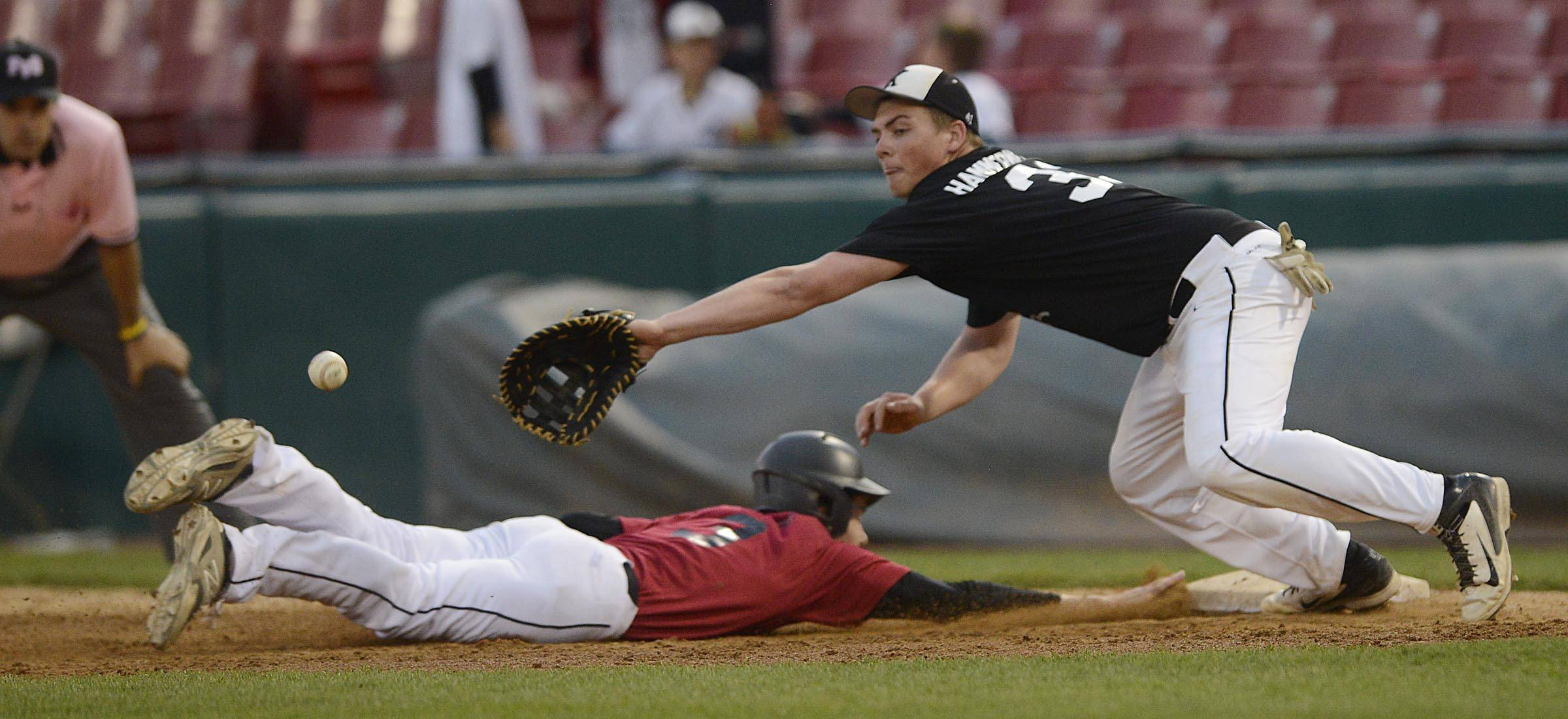 Batavia's Willie Firth dives safely back to first base as Kaneland's Danny Hammermeister dives for the throw Monday.