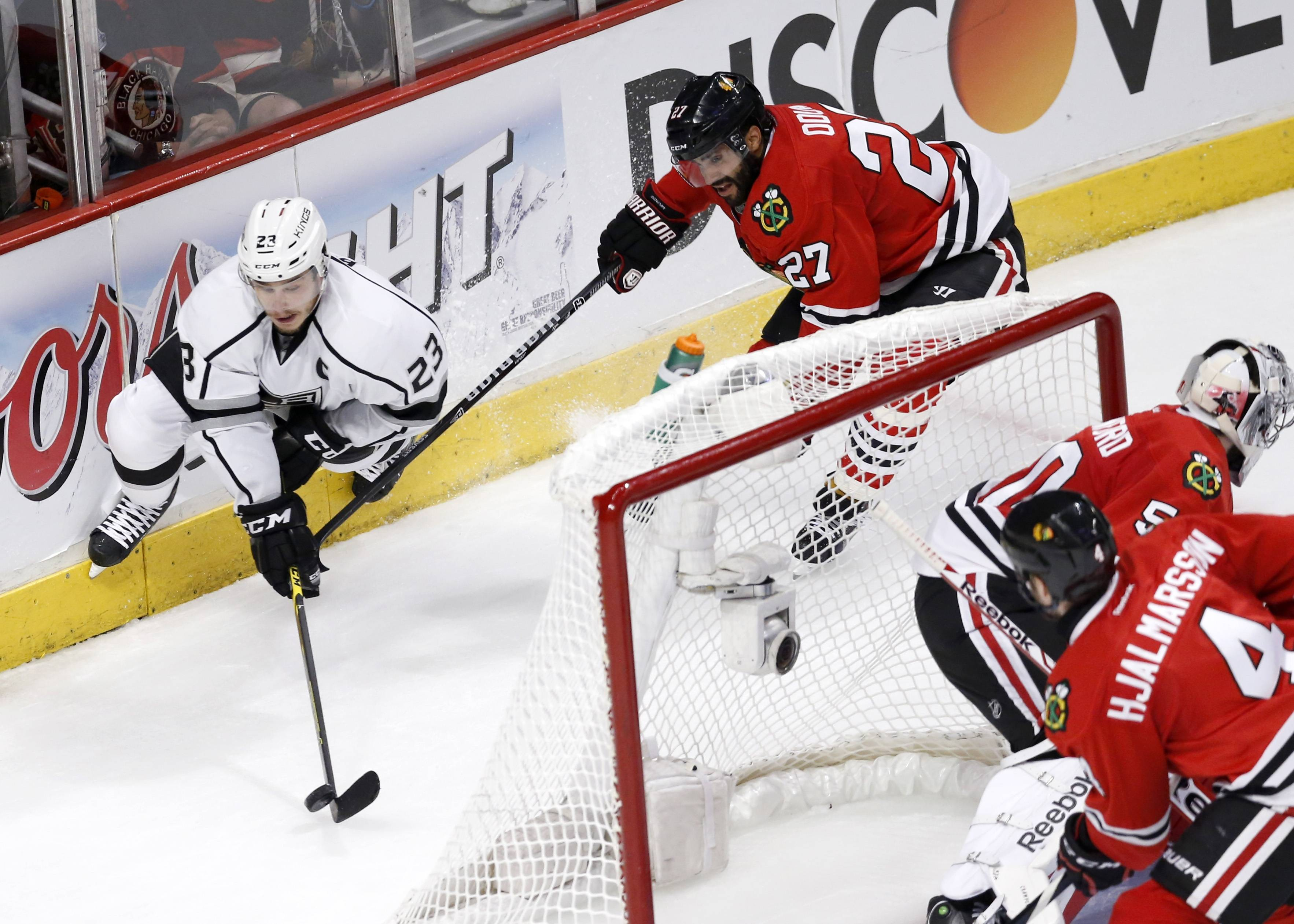 Associated Press In this photo taken Sunday, Chicago Blackhawks defenseman Johnny Oduya (27) forces Los Angeles Kings right wing Dustin Brown (23) into the boards as defenseman Niklas Hjalmarsson (4) watches during the second period of Game 1 of the Western Conference finals in the NHL hockey Stanley Cup playoffs in Chicago. The Blackhawks' defense is playing a key role in this postseason run as the Kings found out how hard it is to score on the defending Stanley Cup champions.