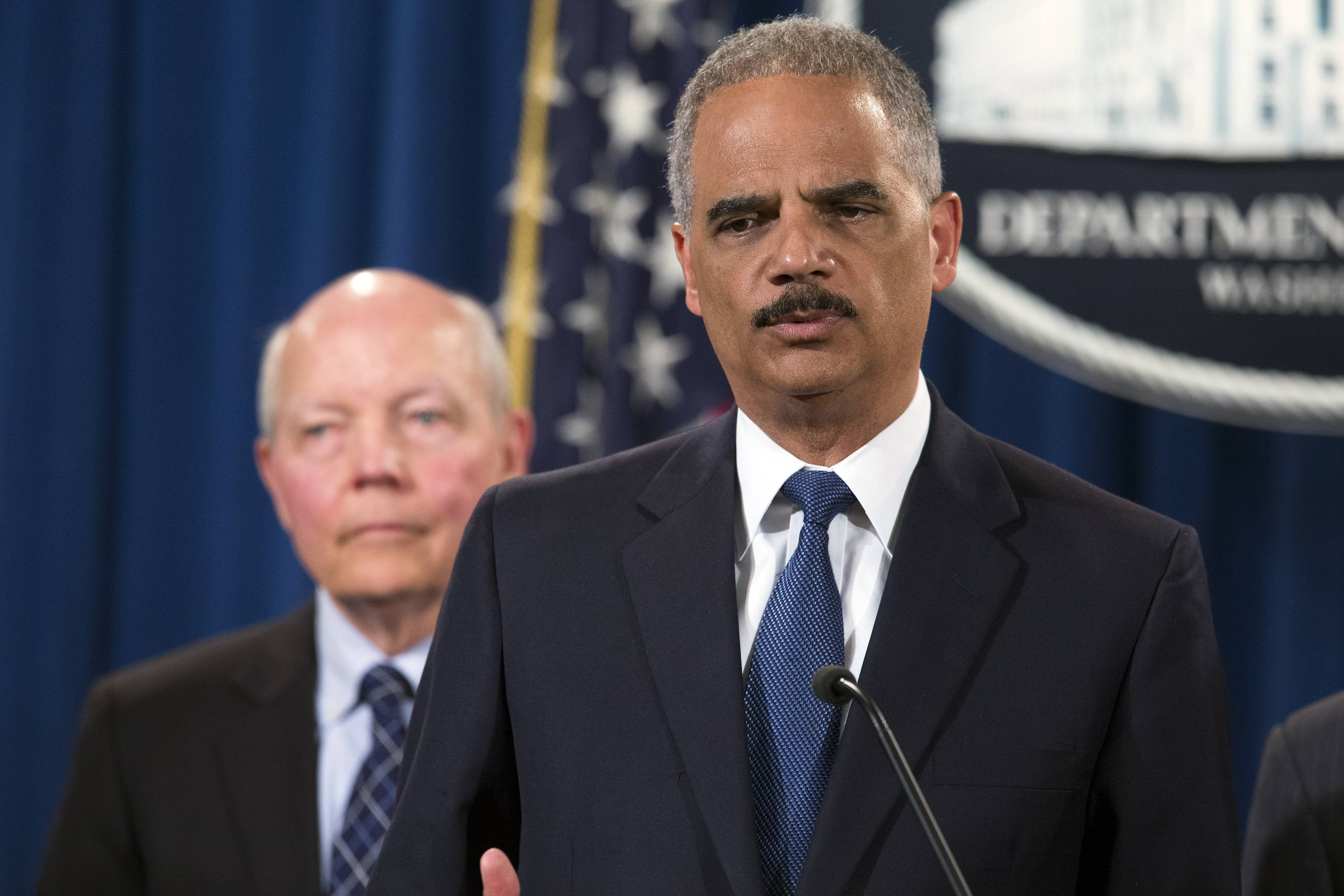 Attorney General Eric Holder, right, with IRS Commissioner John Koskinen listening, outlines Monday how the Justice Department charged Credit Suisse AG with helping wealthy Americans avoid paying taxes through offshore accounts.