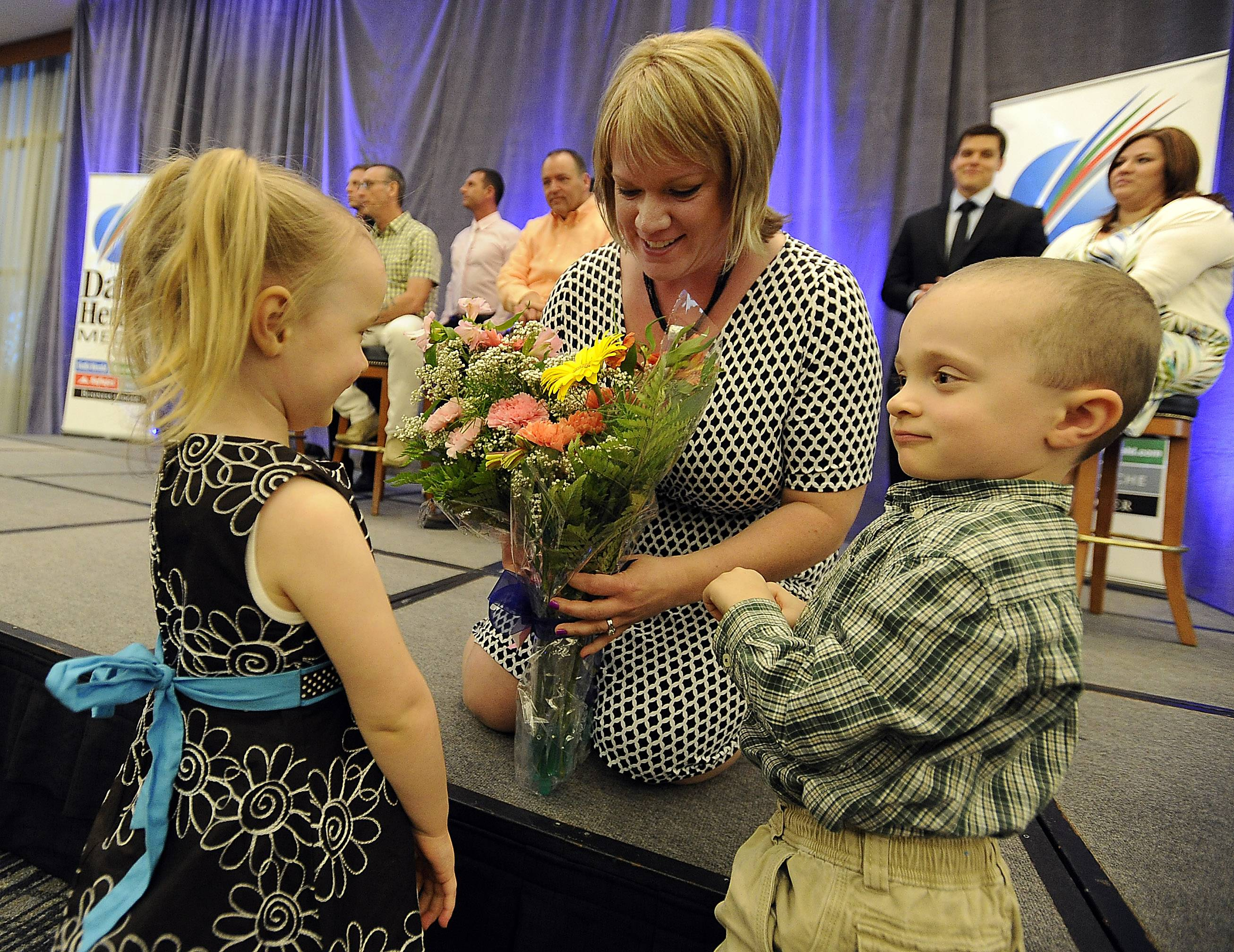 Jillian and Michael Seibert give their mom, Fittest Loser contestant Cheryl Seibert, flowers at the celebration held Thursday at Eaglewood Resort and Spa in Itasca.