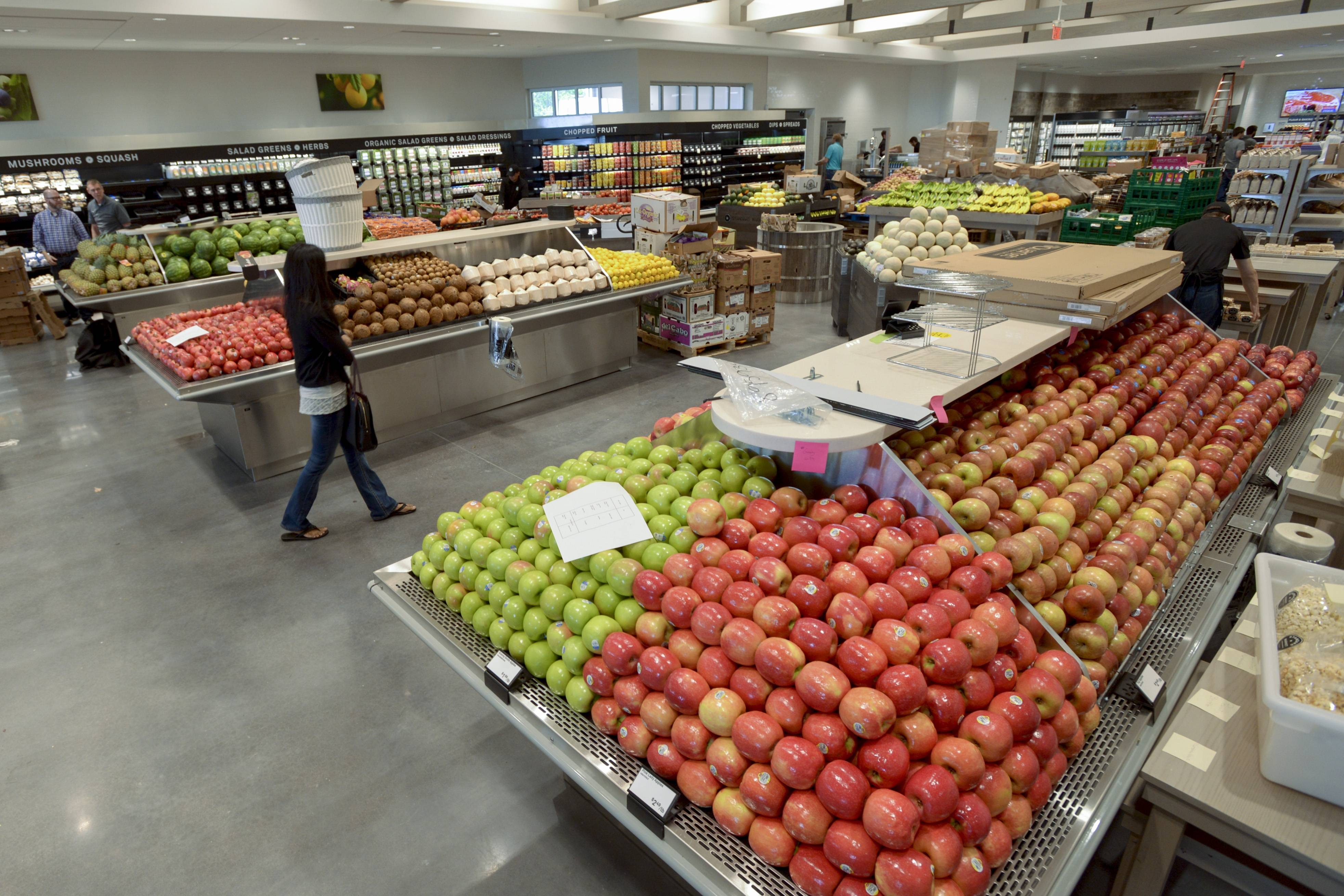 Standard Market in Naperville bustles with pre-opening activity Monday as employees stock produce before the first customers can begin shopping at 8 a.m. Tuesday at 1508 Aurora Ave.