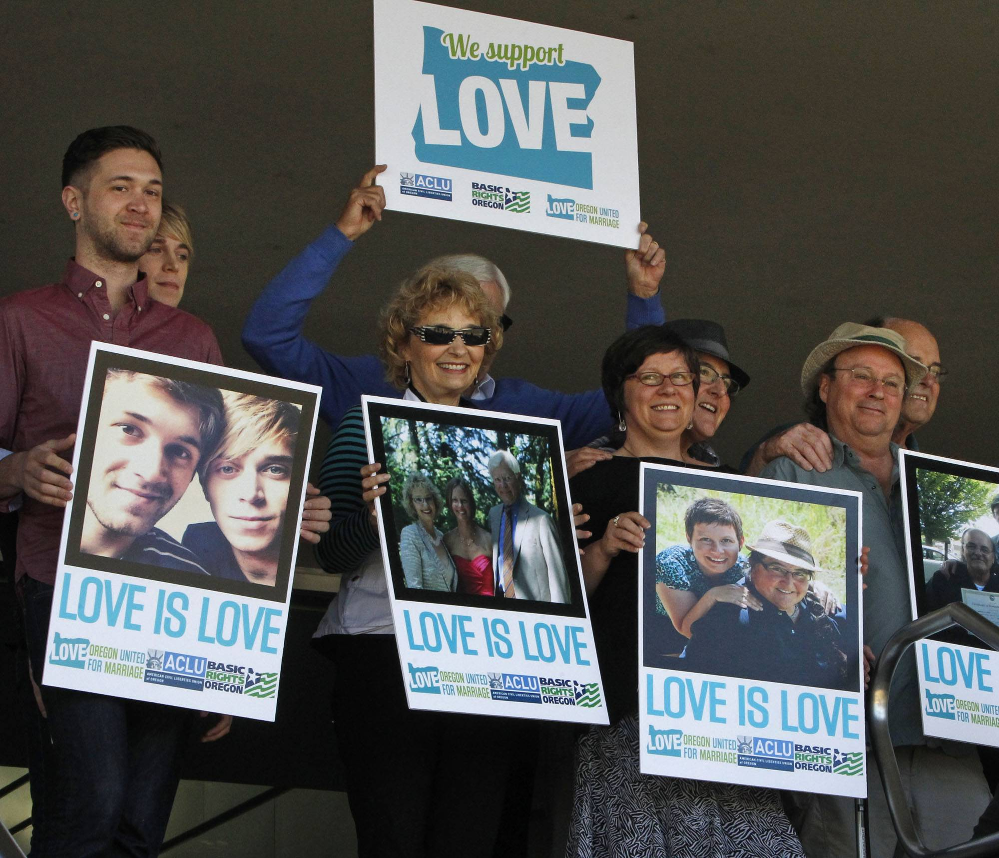 Supporters of same-sex marriage hold photos of themselves and their family members or partners on the steps of the Wayne L Morse U.S. Courthouse Wednesday in Eugene, Ore. A federal judge on Monday struck down Oregon's voter-approved ban on gay marriage, saying it is unconstitutional.