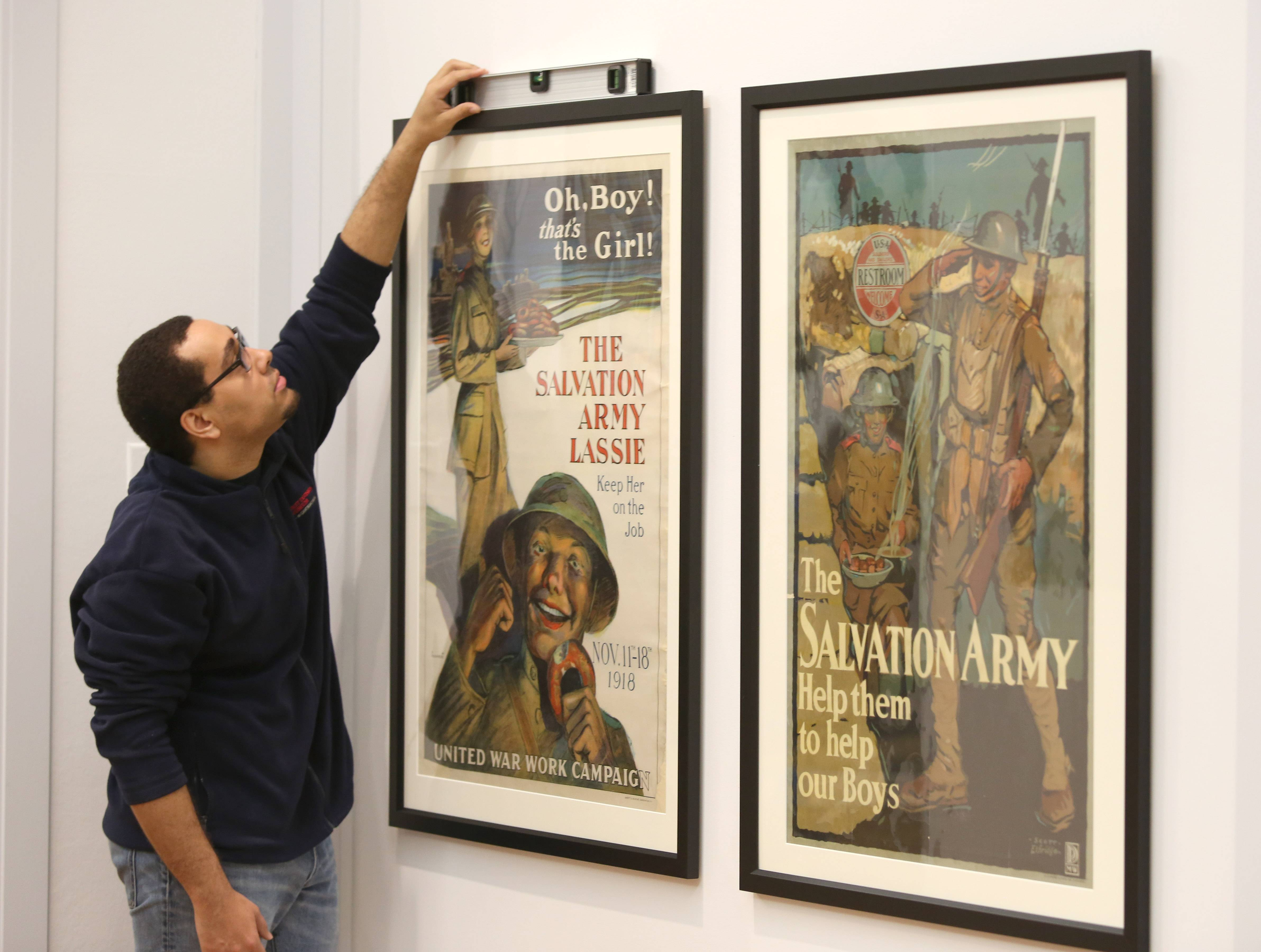 Exhibit designer Jaron Keener levels framed posters from First Division Museum's World War I collection.