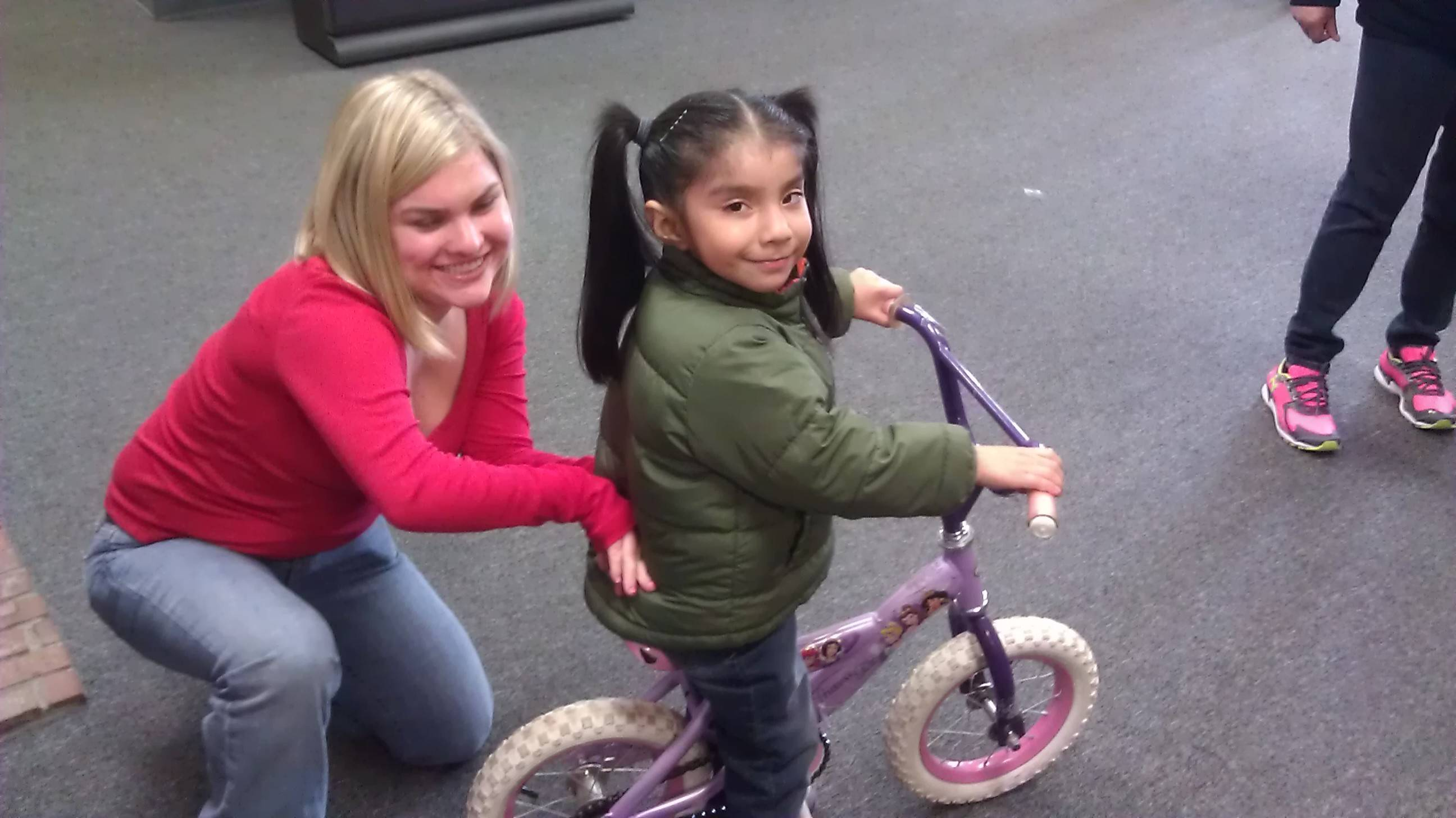 Lisa Johnson of the YMCA helps fit Laura Hernandez with her first bike last fall at the Palatine Opportunity Center. Laura didn't win a bike at the Day of Giving, but Wayne Mikes brought bikes in spring for those children who did not get one in November.