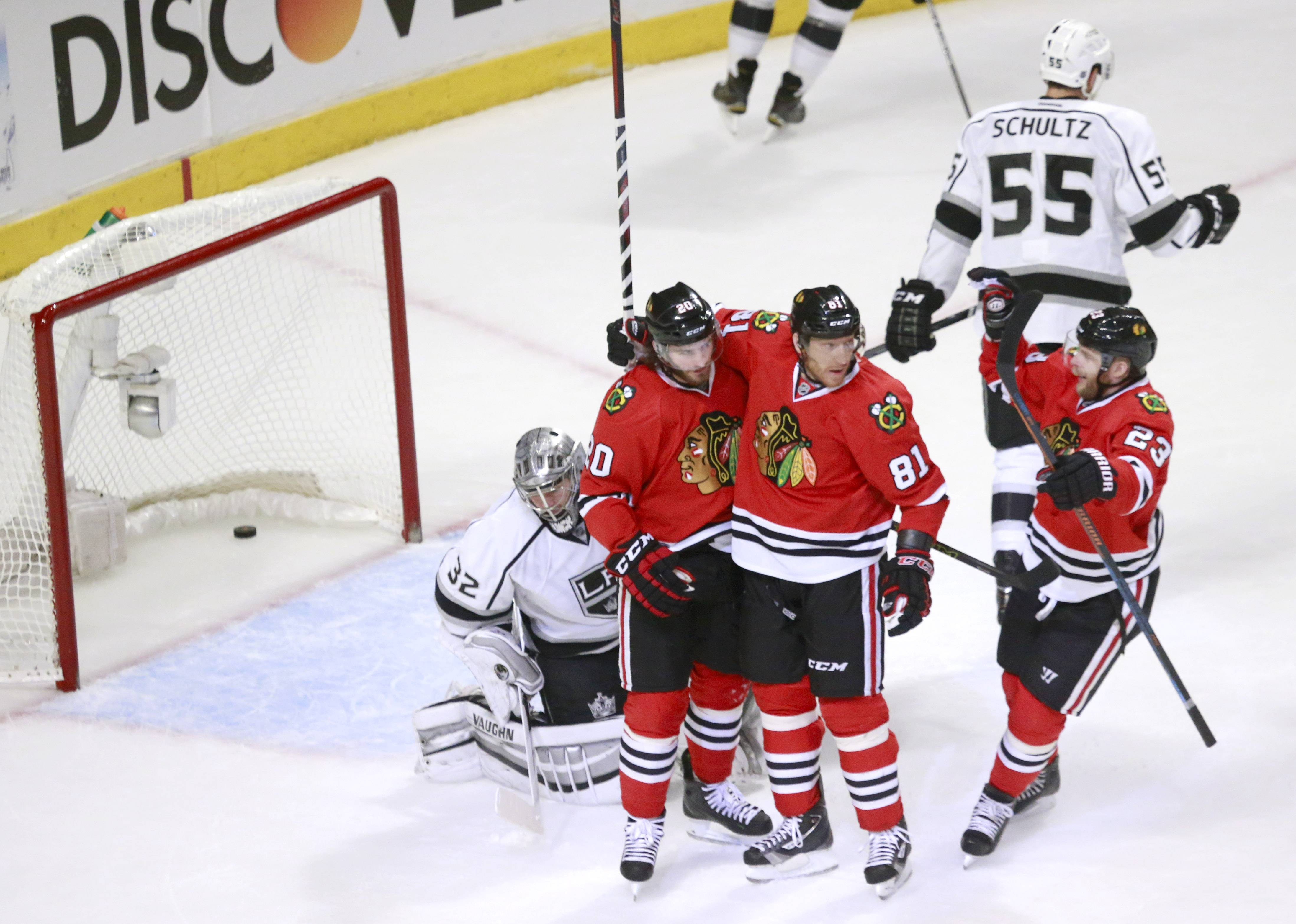 Blackhawks left wing Brandon Saad (20), Marian Hossa (81) and Kris Versteeg (23) celebrate Saad's goal against Los Angeles Kings goalie Jonathan Quick (32) as Jeff Schultz (55) skates away during the first period.