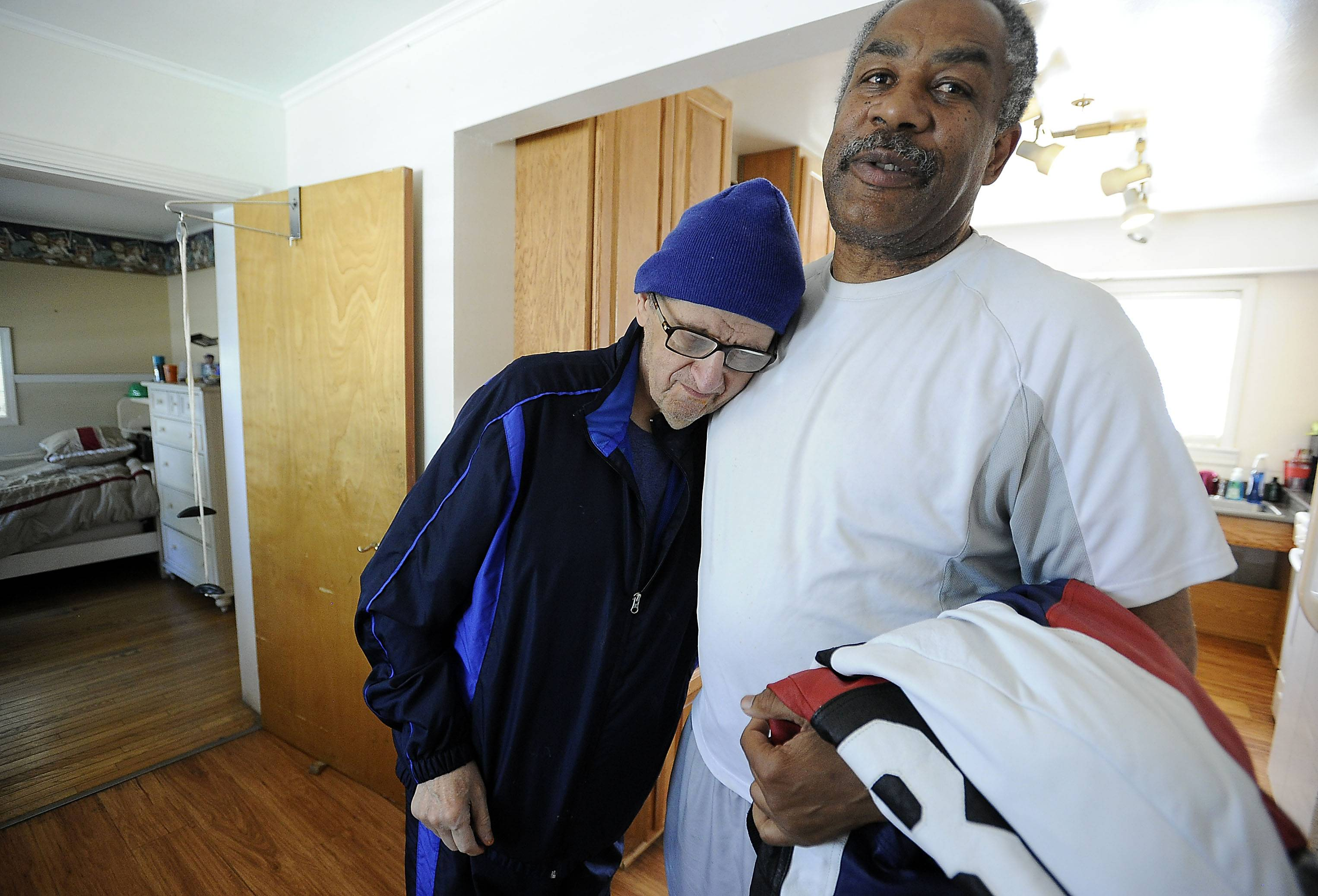 Just home from work, Cambridge House resident Billy Yacilla hugs caregiver Gregory Mathis, who has received only $1.70 in raises in his 12 years on the job.