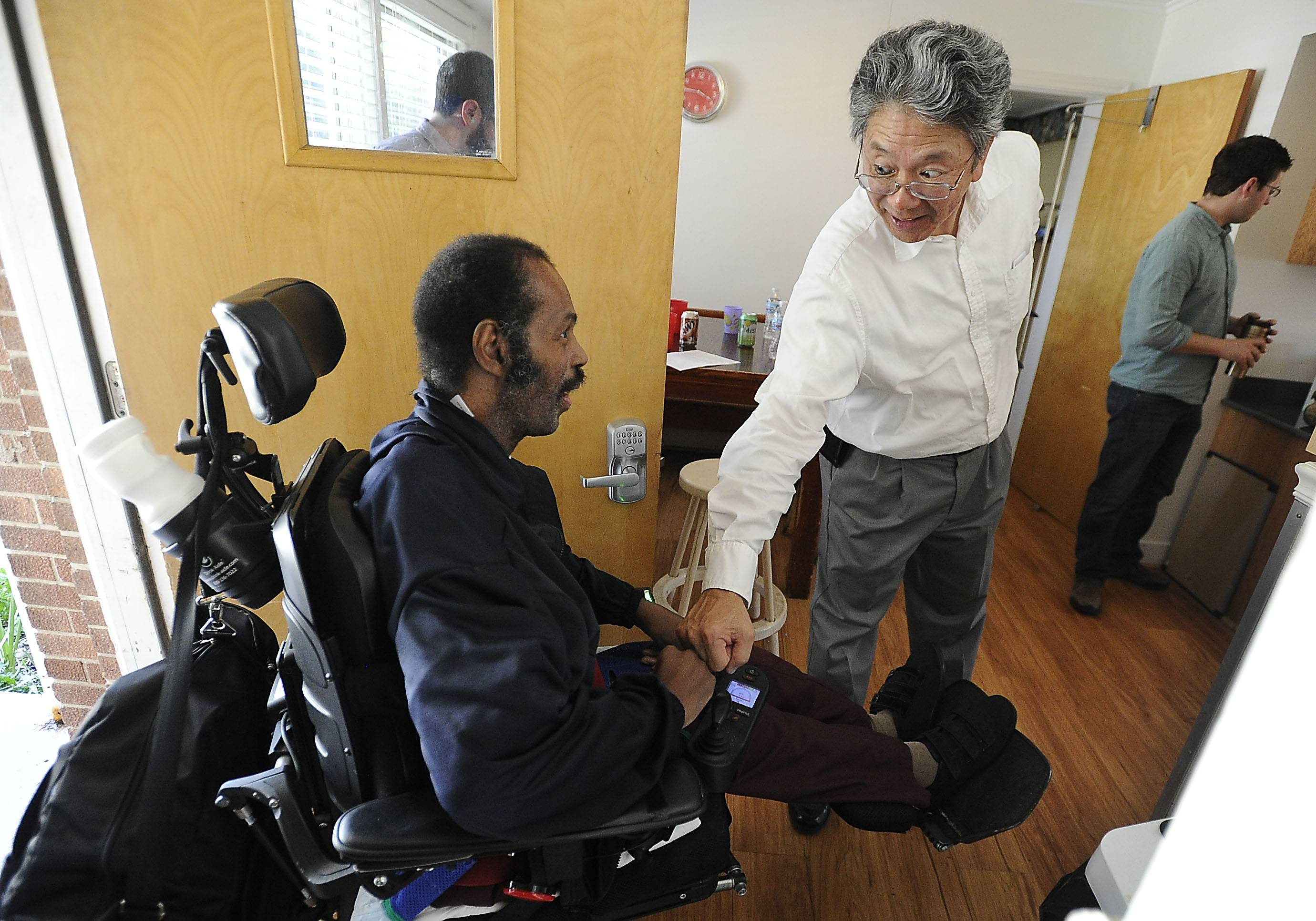 Cambridge House resident John Davis gives a fist bump to Robert Okazaki of Avenues to Independence.