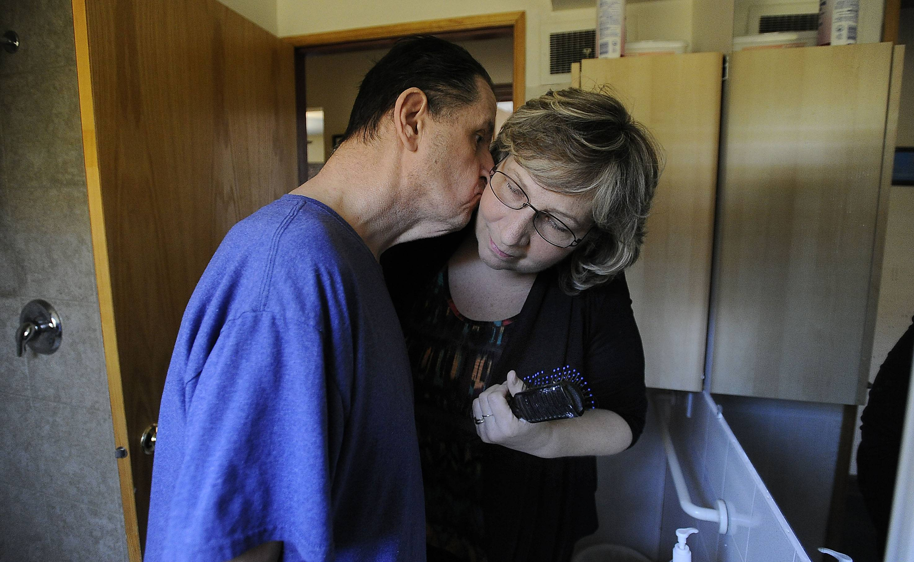 Billy Yacilla gives a kiss to caregiver Neoma Spencer of Hoffman Estates after she combed his hair at Cambridge House.
