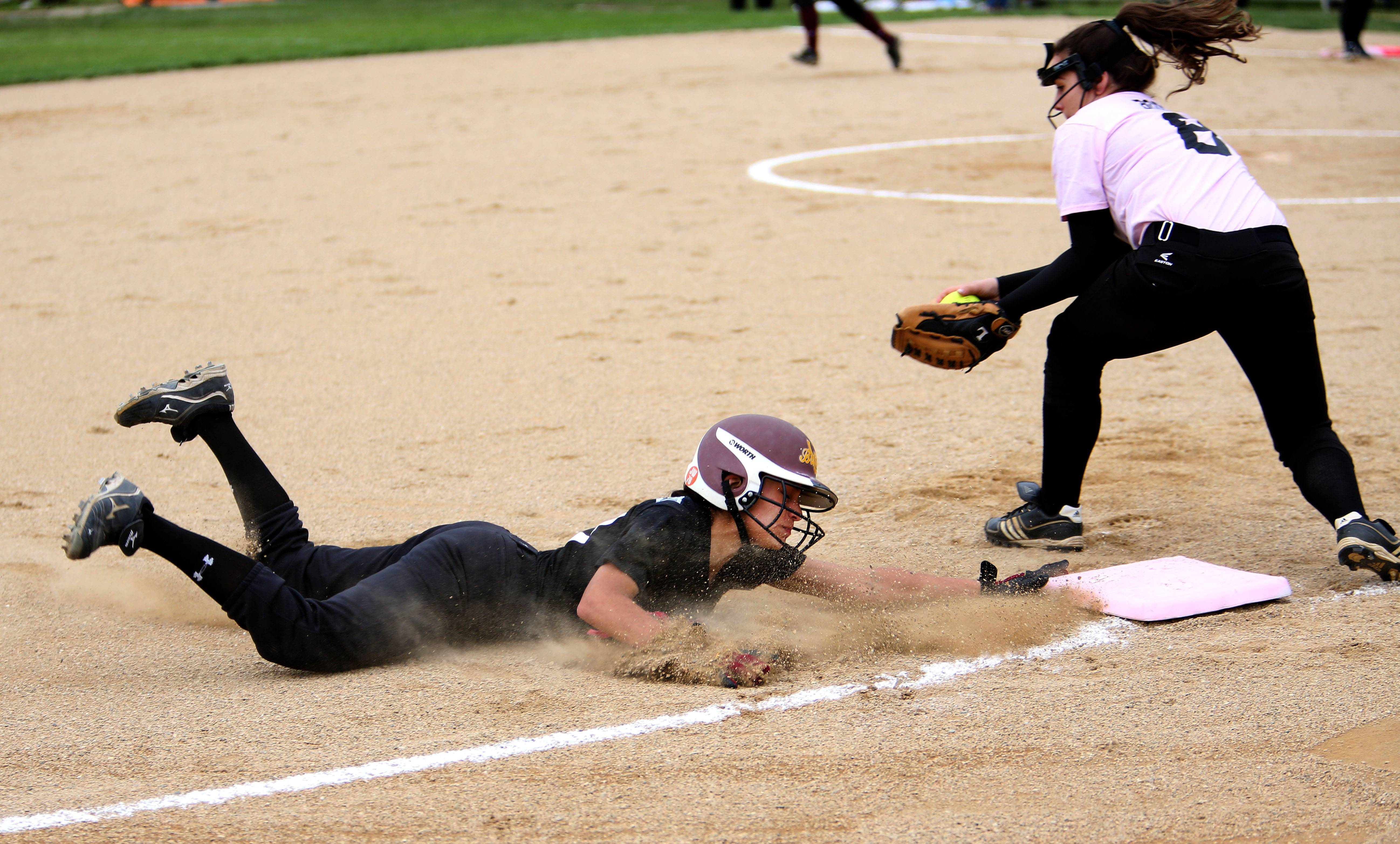 Montini's Christina Barrett steals third base in the second inning as Wheaton Academy's Gina Graff tries to make the tag during softball action in Lombard on Monday.