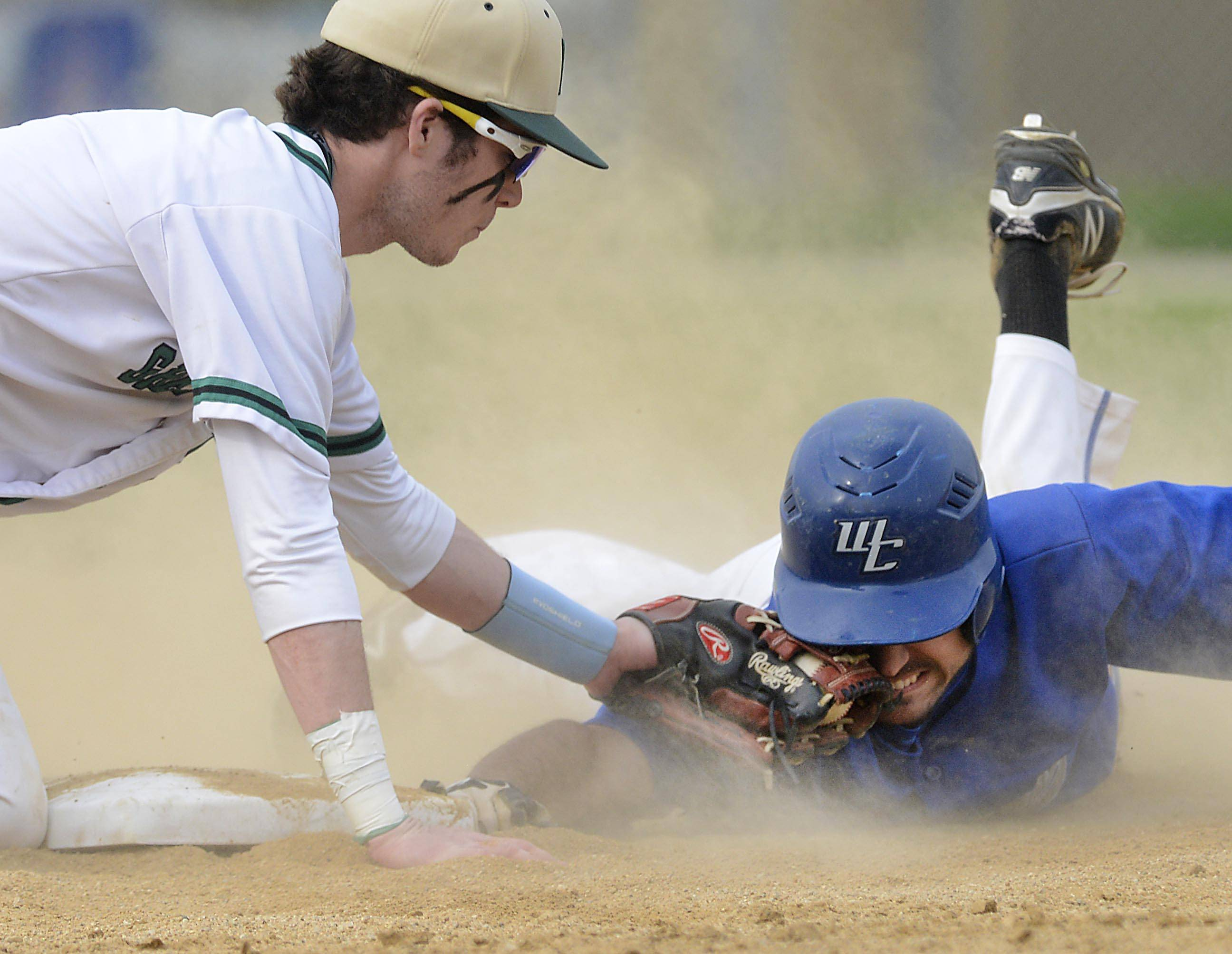 St. Edward's Ryan Nudd tags Westminster Christian's Frankie Angiulo in the face Monday in the Class 2A regional game at Wing Park in Elgin. Angiulo was called safe and a run scored in the third inning.