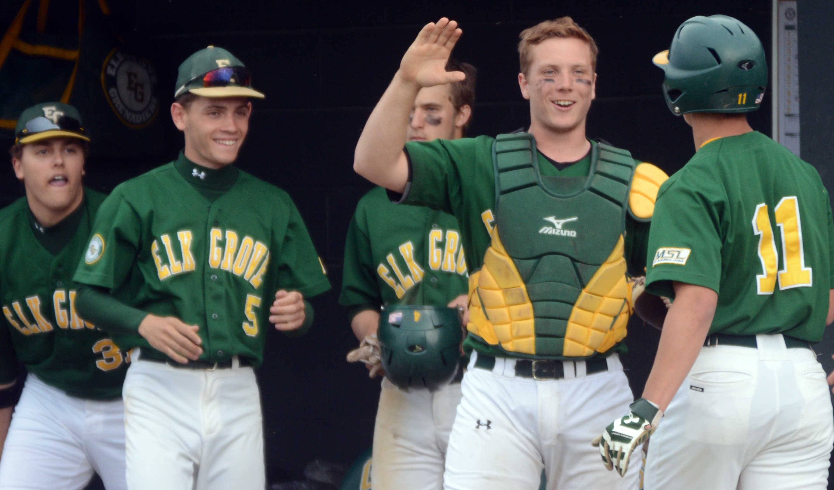 Elk Grove's Brandon Post, right, is received in the dugout by catcher Sean Fege, center, and others after Post scored against Schaumburg in Elk Grove's 6-2 win.
