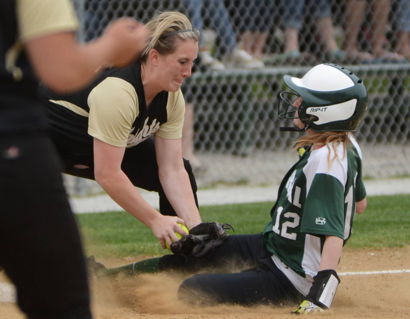 Grayslake North's Nikki Livengood, left, applies the tag to get Grayslake Central's Shelby White out at third during Monday's game.
