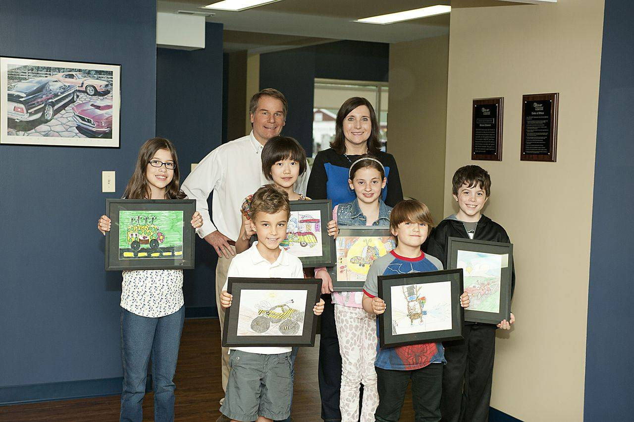 Douglas Automotive owners, Doug and Janet McAllister, and the winners of the 2014 art contest