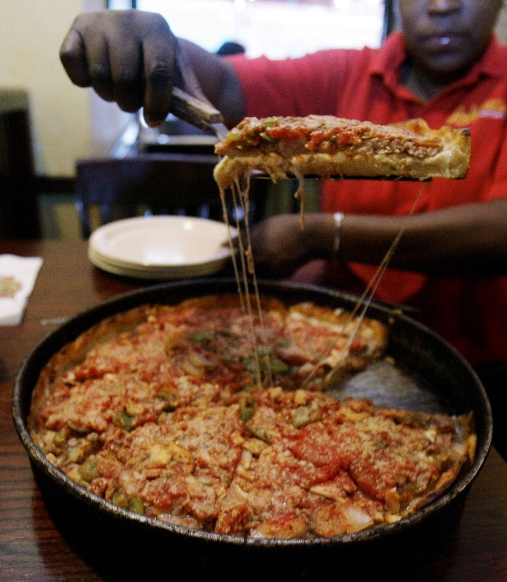 ASSOCIATED PRESS A slice of Lou Malnati's Pizza is served. The 1½ inch thick legendary pie, loaded with sausage, mushrooms, pepperoni, onions was invented in Chicago. New Yorkers prefer flat pizza.