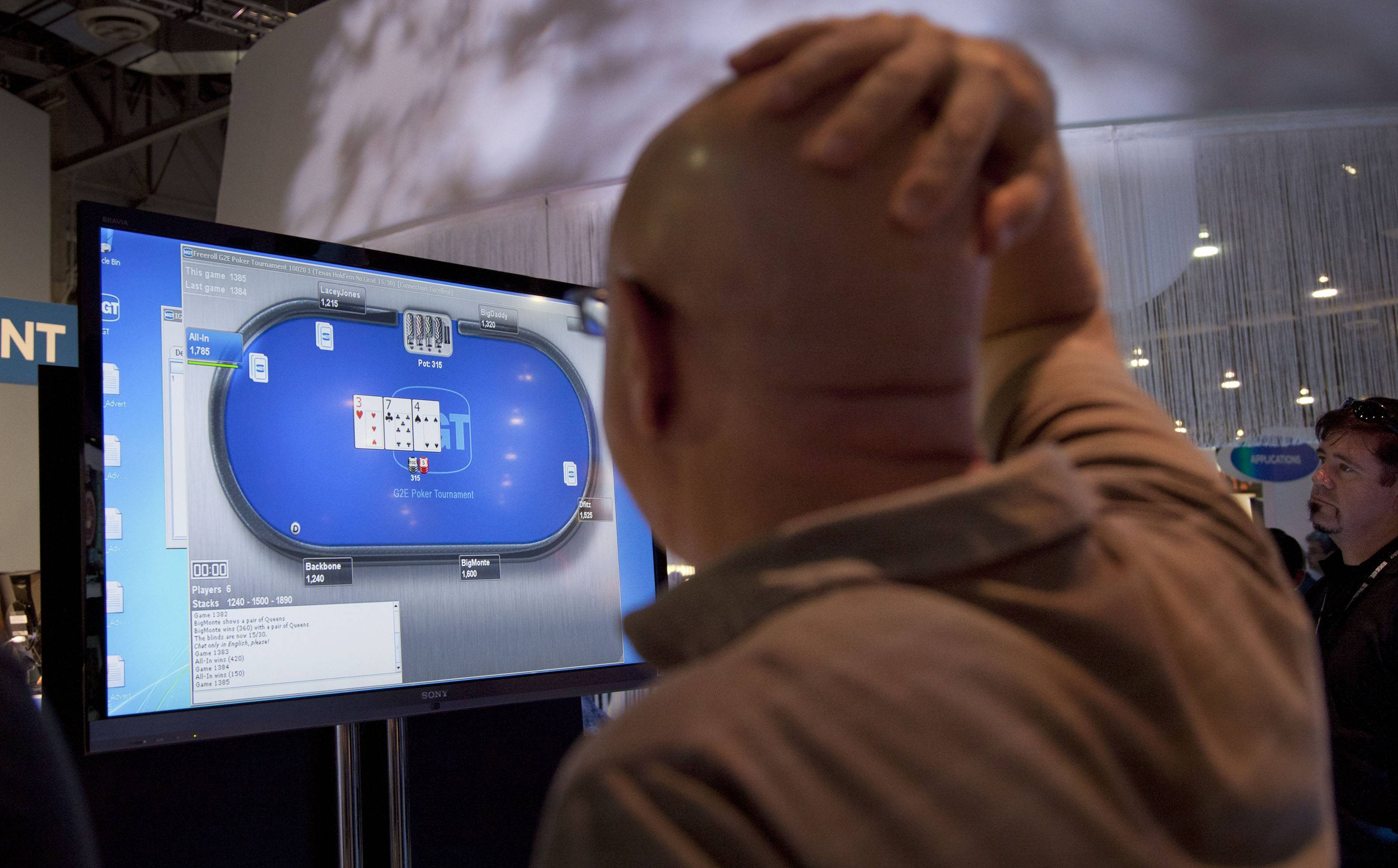 Associated Press Photo casino industry representatives and exhibitors watch an online poker game at the industry's G2E gaming conference in Las Vegas.