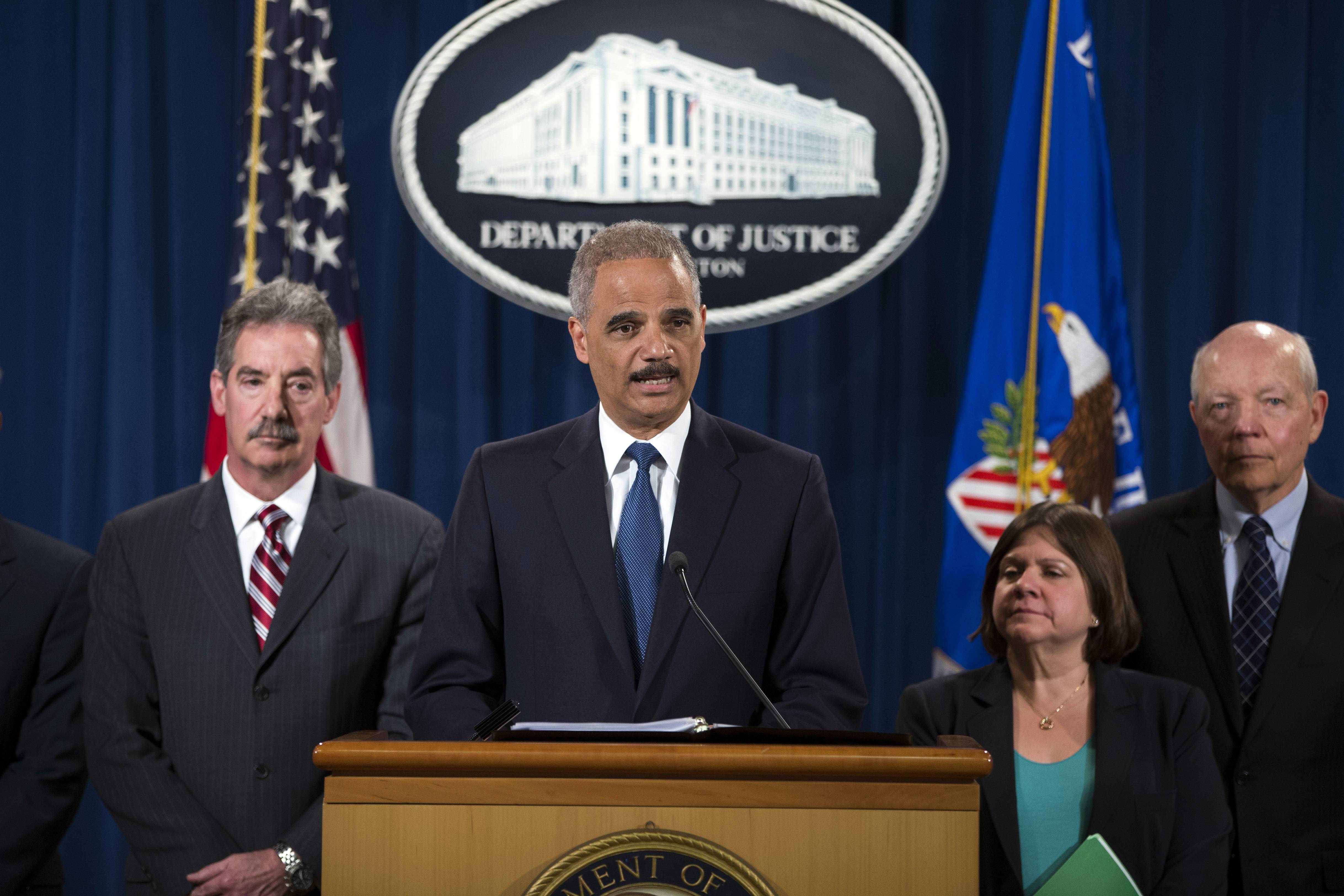Attorney General Eric Holder, center, speaks during a news conference at the Justice Department, on Monday in Washington. The Justice Department charged Credit Suisse AG with helping wealthy Americans avoid paying taxes through offshore accounts, and a person familiar with the matter said the European bank has agreed to pay about $2.6 billion in penalties. From left, Deputy Attorney General James Cole, Holder, Assistant Attorney General for the Tax Division Kathryn Keneally, and IRS Commissioner John Koskinen