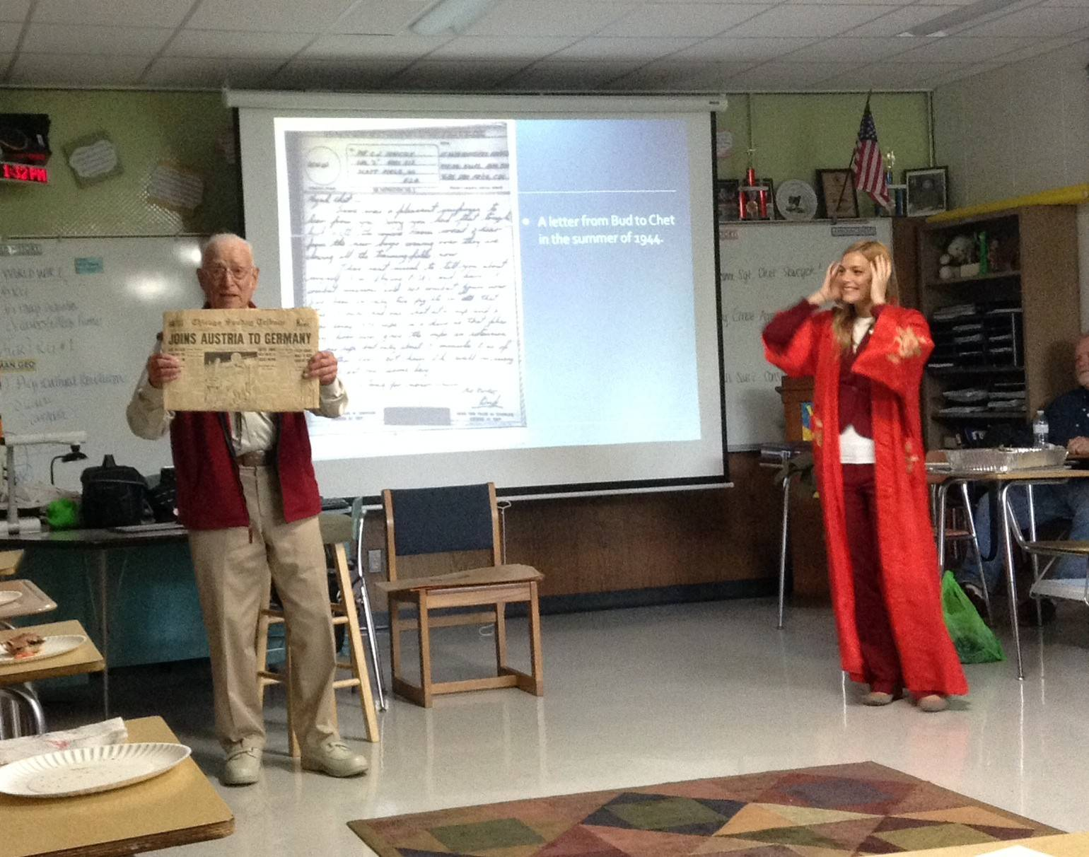 Chester Sewcyck, left, shows a newspaper headline from the World War II era to the Elk Grove High School U.S. History class taught by Stephanie Kezios, right, while visiting with students Tuesday. Sewcyck, an 88-year-old veteran of World War II, was stationed in the Pacific from 1944 through 1946.