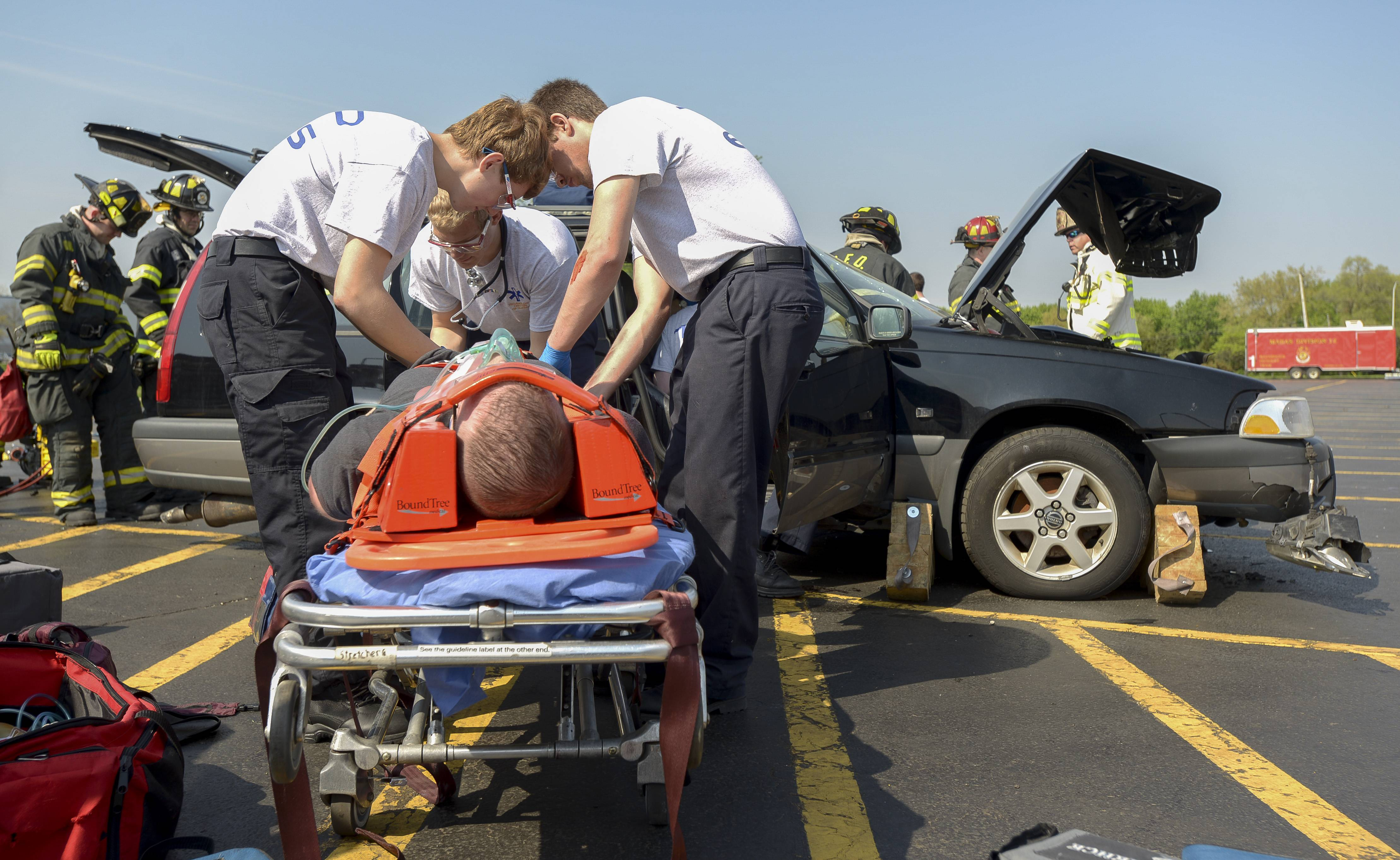 High school students in the EMT program at the Technology Center of DuPage work with Addison firefighters Tuesday during a drill involving a two-vehicle accident at the Addison school.