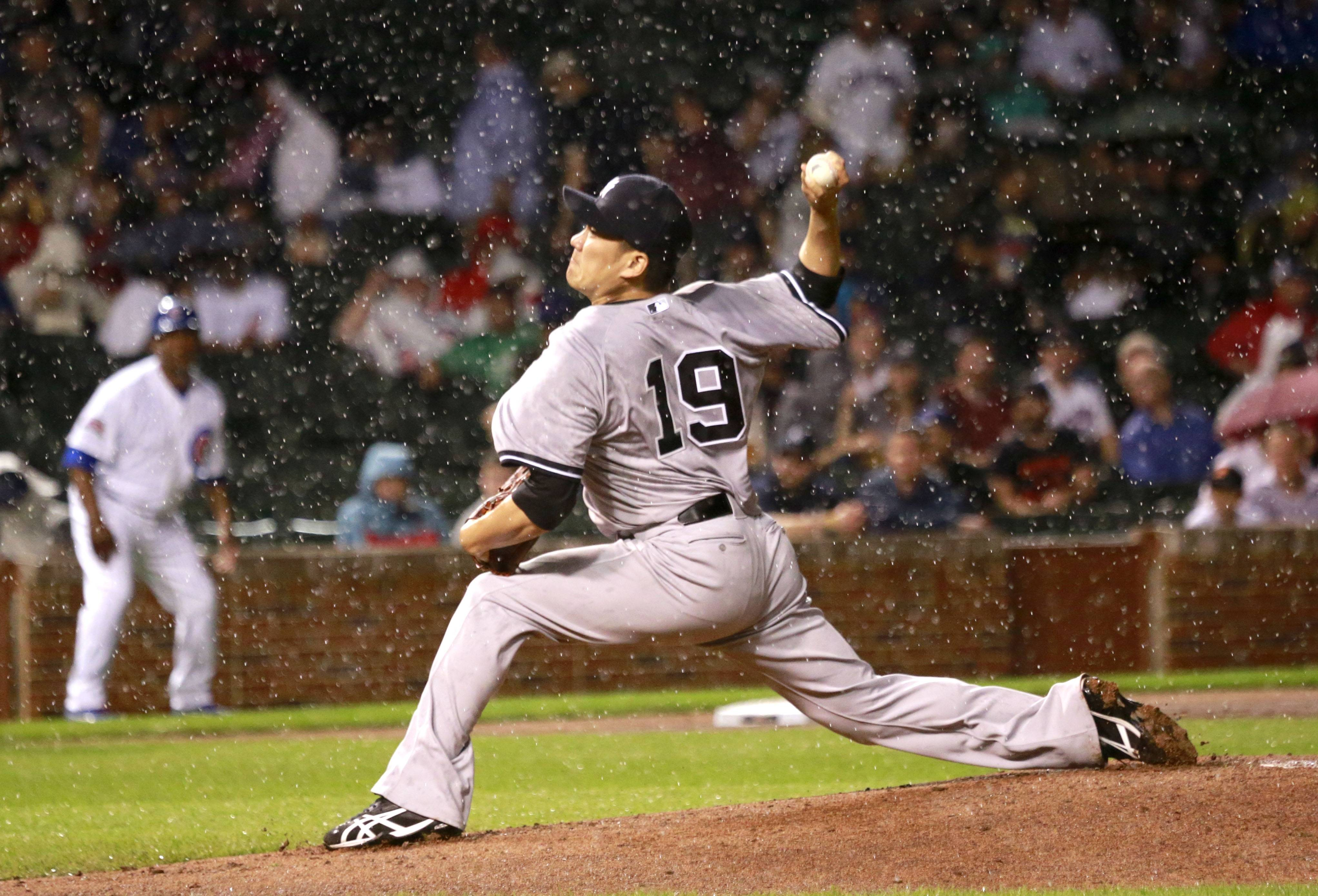 New York Yankees starting pitcher Masahiro Tanaka delivers in a steady rain during the third inning of an interleague baseball game against the Chicago Cubs on Tuesday in Chicago.