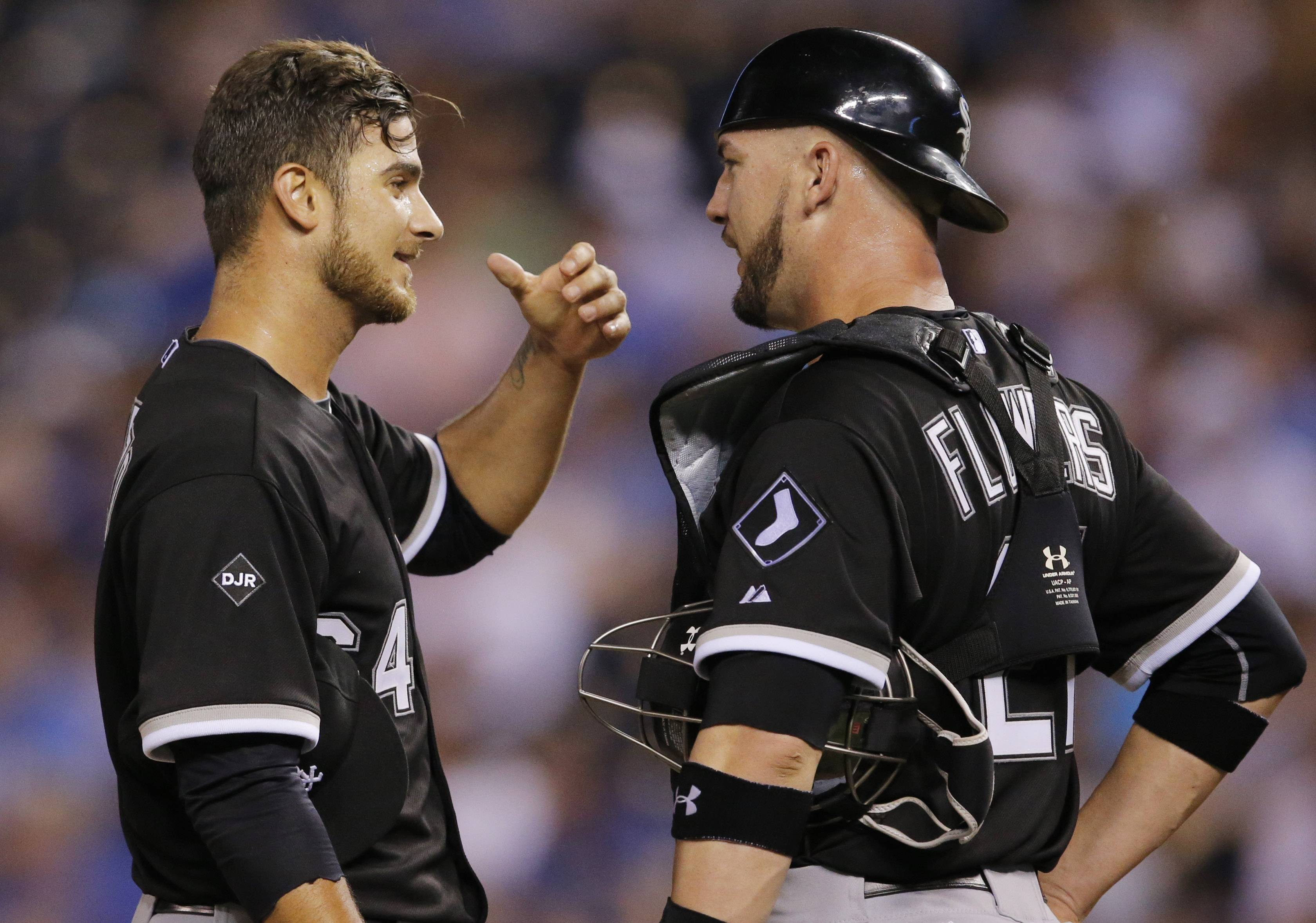 Chicago White Sox starting pitcher Andre Rienzo, left, talks with catcher Tyler Flowers (21) during the sixth inning of a baseball game Tuesday against the Kansas City Royals at Kauffman Stadium in Kansas City, Mo.