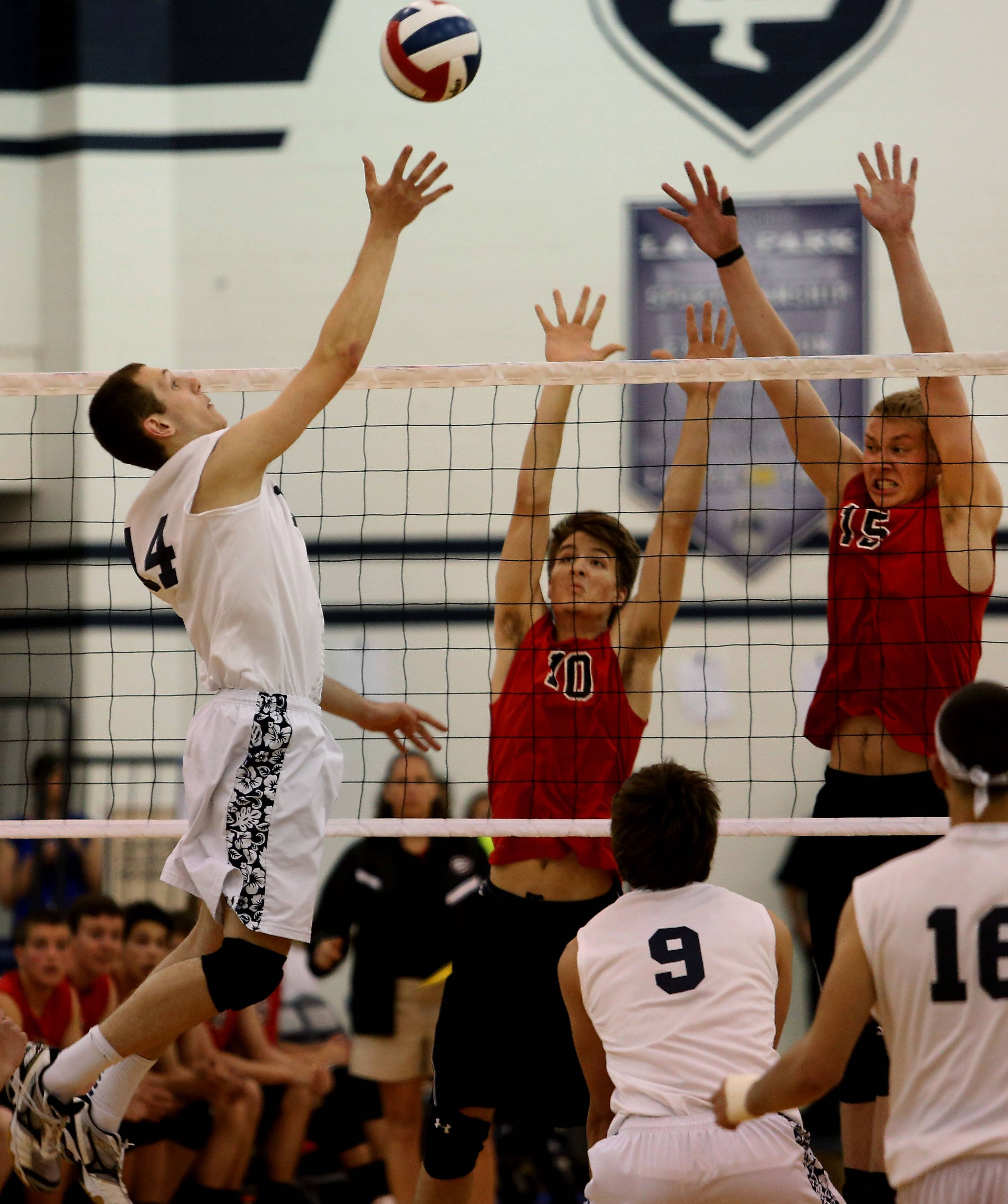 Jeff Yost, left, of Lake Park goes up for the ball as Jamie Wareham (10) and Erik Fiebrandt (15) of Glenbard East defend during boys volleyball action in Roselle on Tuesday.