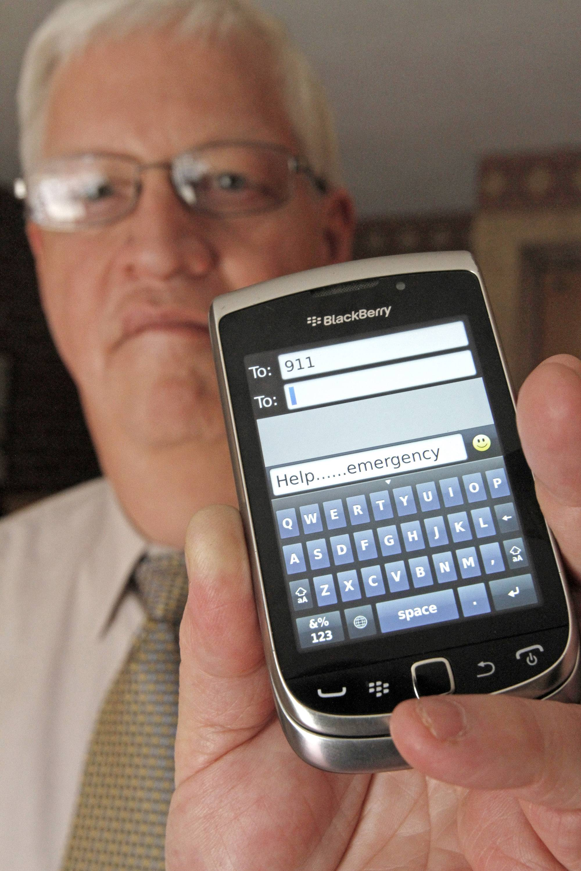 David Tucker, executive director of Vermont's Enhanced 911 Board, holds a smart phone in Montpelier, Vt. Tucker says the state is the first in the country where customers of the four major wireless carriers can send text messages to 911.