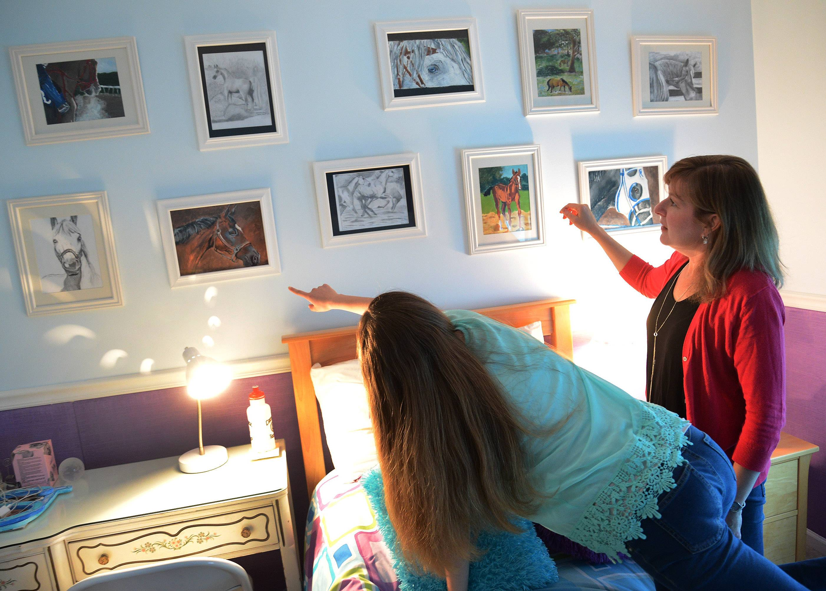 Millburn Middle School eighth-grade artist Sydney Janda and her mom, Stacy, show visitors some of her early work.