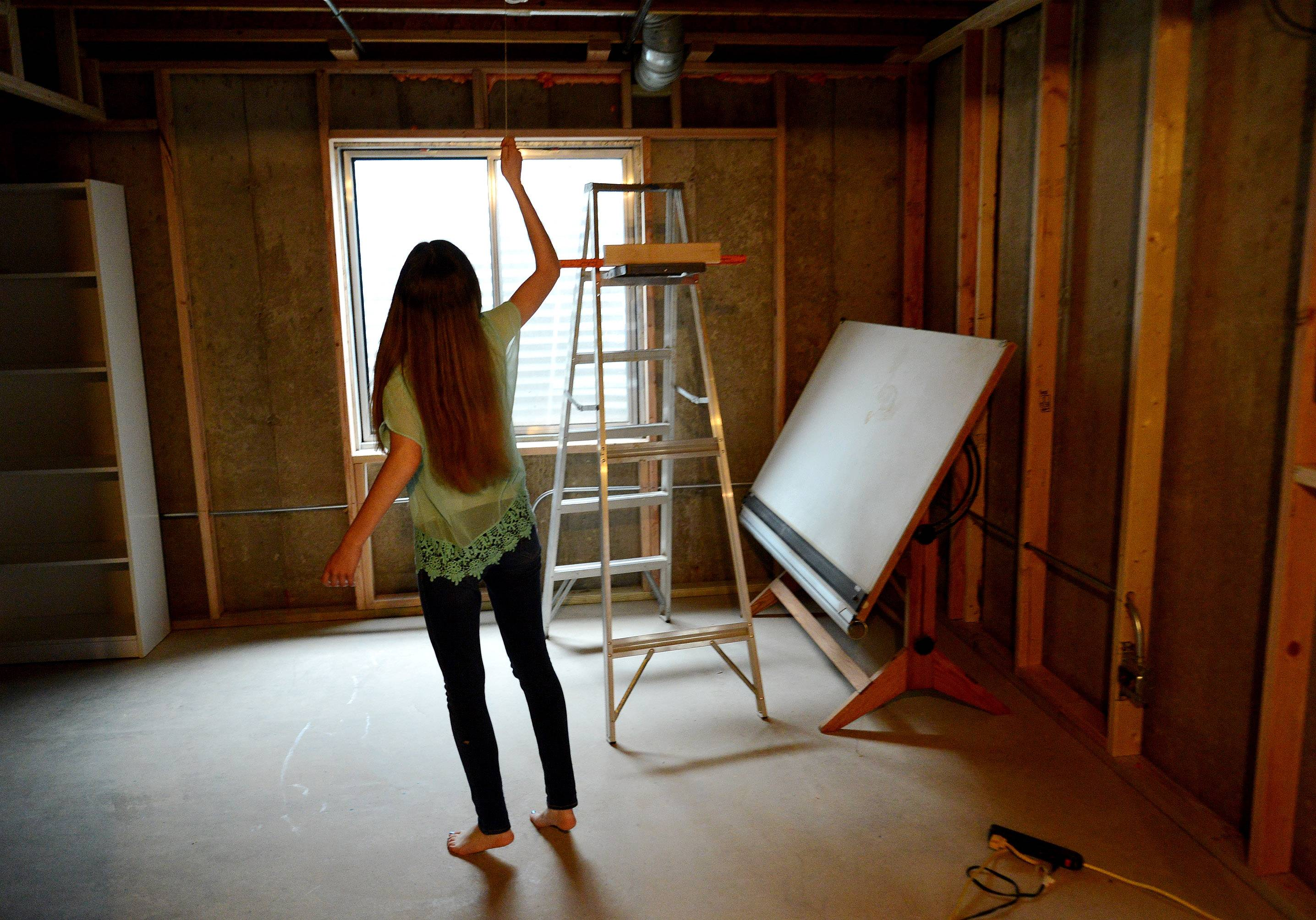 Sydney Janda, an eighth-grader at Milburn Middle School, turns on the light in what will be a studio in the family basement.