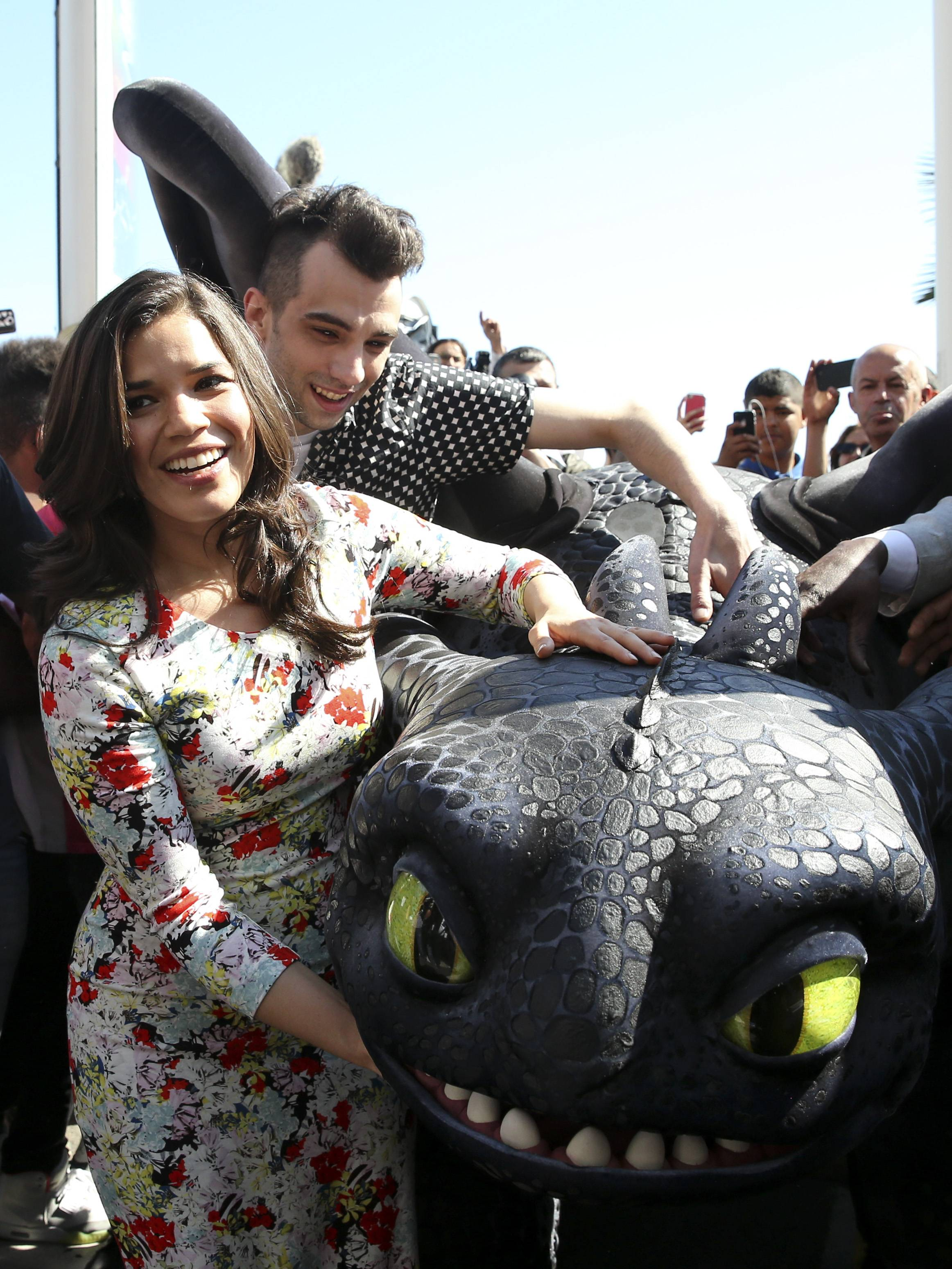 "America Ferrera and actor Jay Baruchel have a little fun with a model dragon during a photo call for ""How to Train Your Dragon 2"" at the Cannes Film Festival."