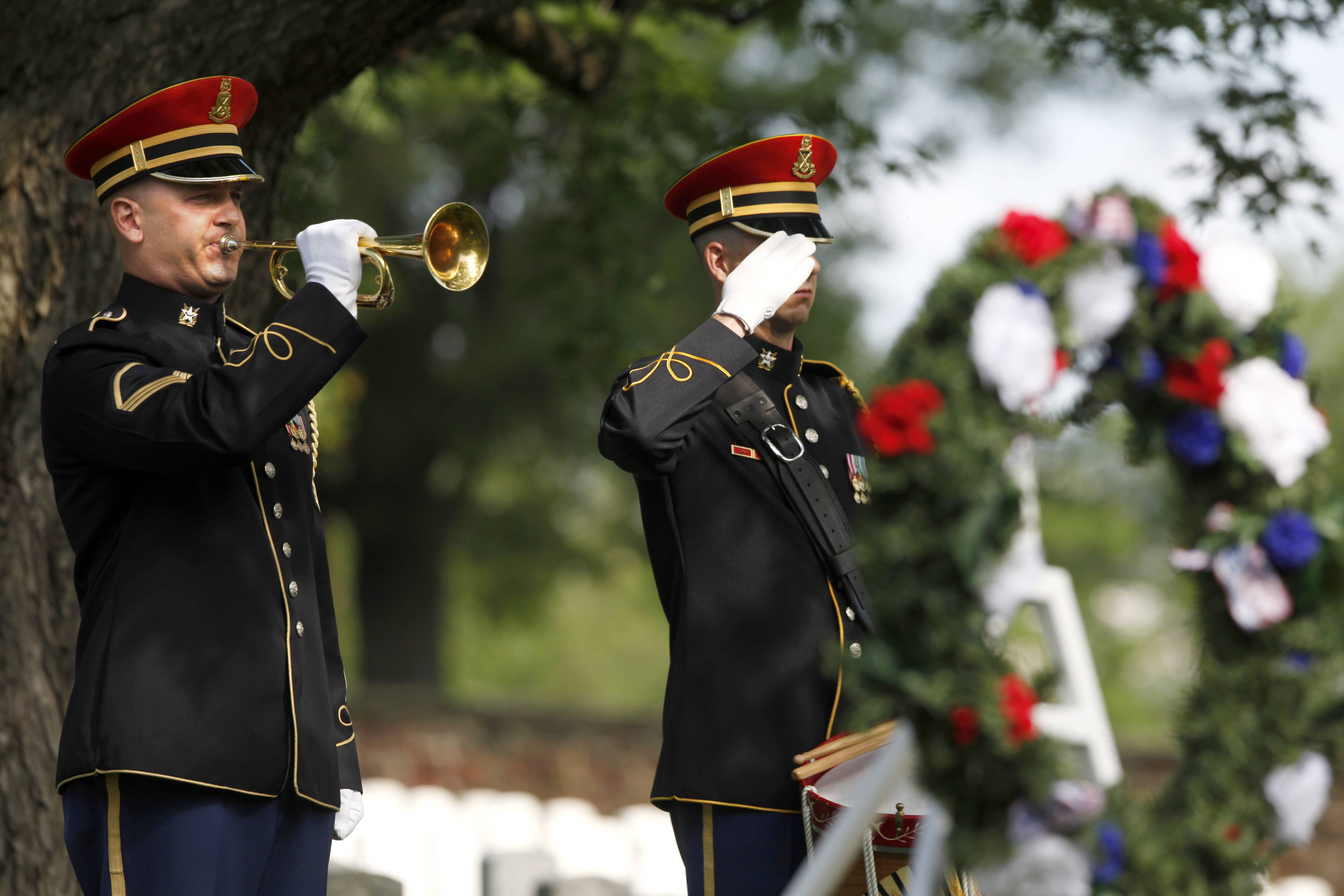 "An Army honor guard bugler plays ""Taps"" after a wreath was laid at the grave site of Army Pvt. William Christman, the first military burial at the cemetery, marking the beginning of commemorations of the 150th anniversary of Arlington National Cemetery in Arlington, Va."