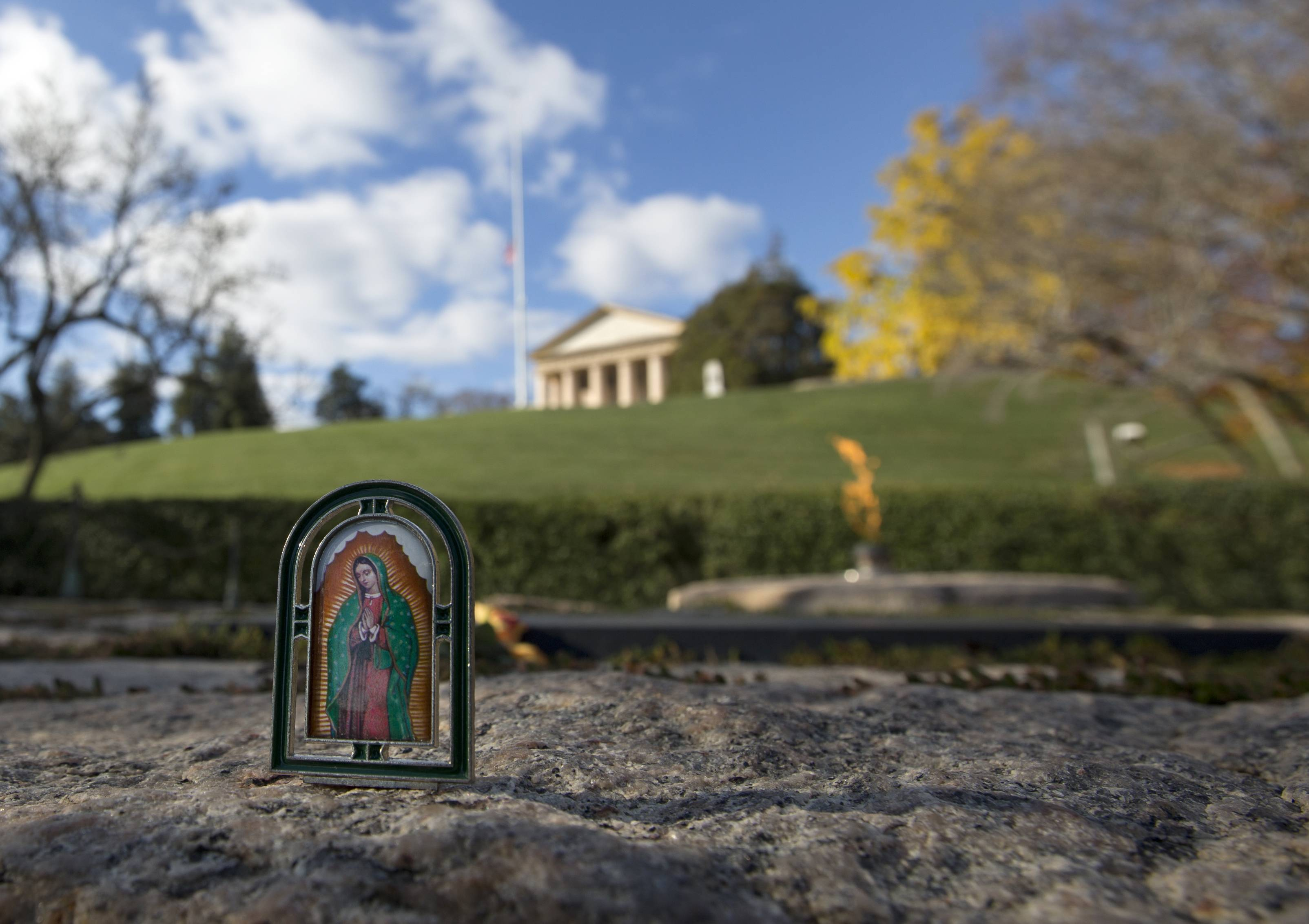 A small image of the Blessed Virgin Mary stands on the stone surrounding the eternal flame and grave site of President John F. Kennedy at Arlington National Cemetery in Arlington, Va. The Arlington House, the Robert E. Lee Memorial sits at the top of the hill overlooking the grave site.