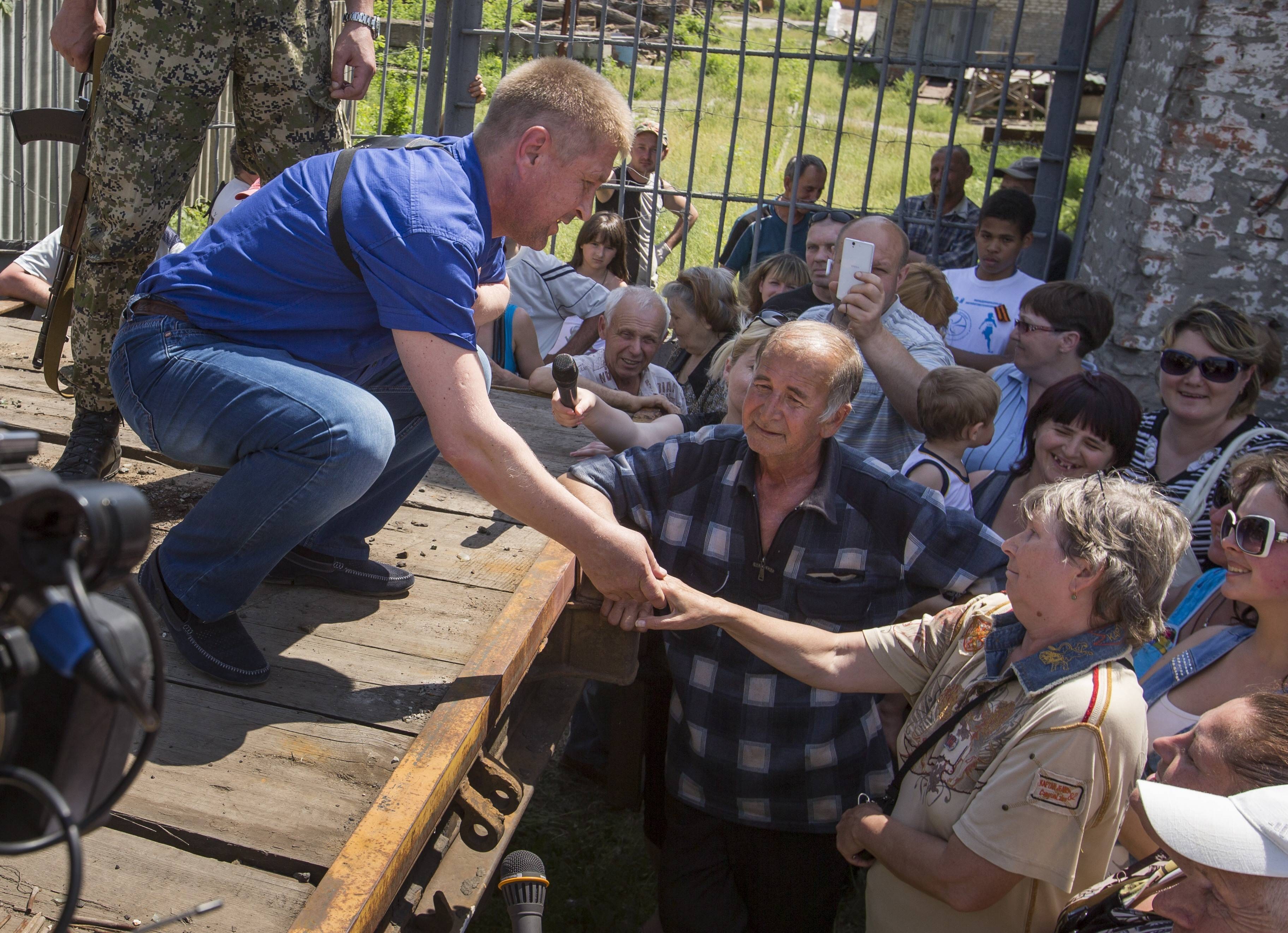 Vyacheslav Ponomarev, left, the self-proclaimed mayor of Slovyansk, shakes hands with a woman during his meeting with local citizens whose homes were ruined in a shelling in Slovyansk, eastern Ukraine. Residents of Slovyansk sounded exasperated and angry with both the warring sides.