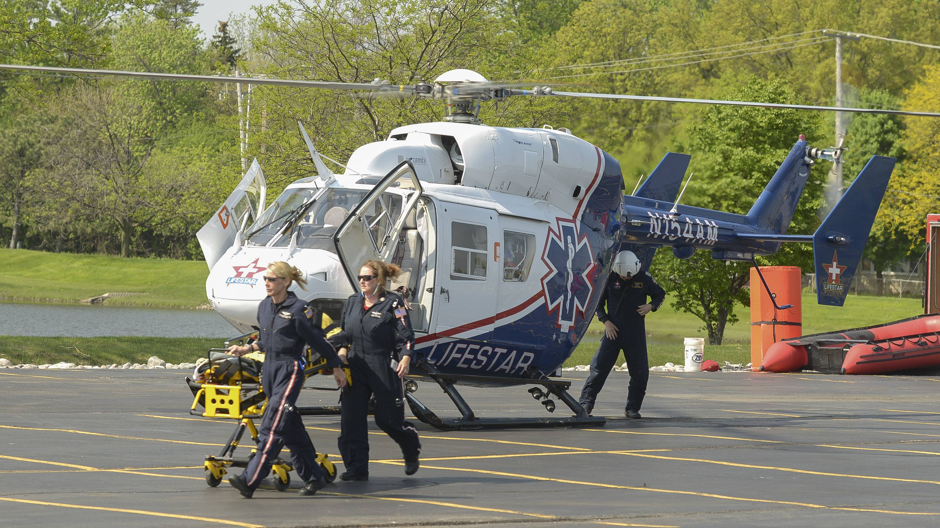 A Lifestar helicopter crew lands in the parking lot of the Technology Center of DuPage Tuesday to participate in a drill involving the school's students in the fire science-EMT and criminal justice programs.