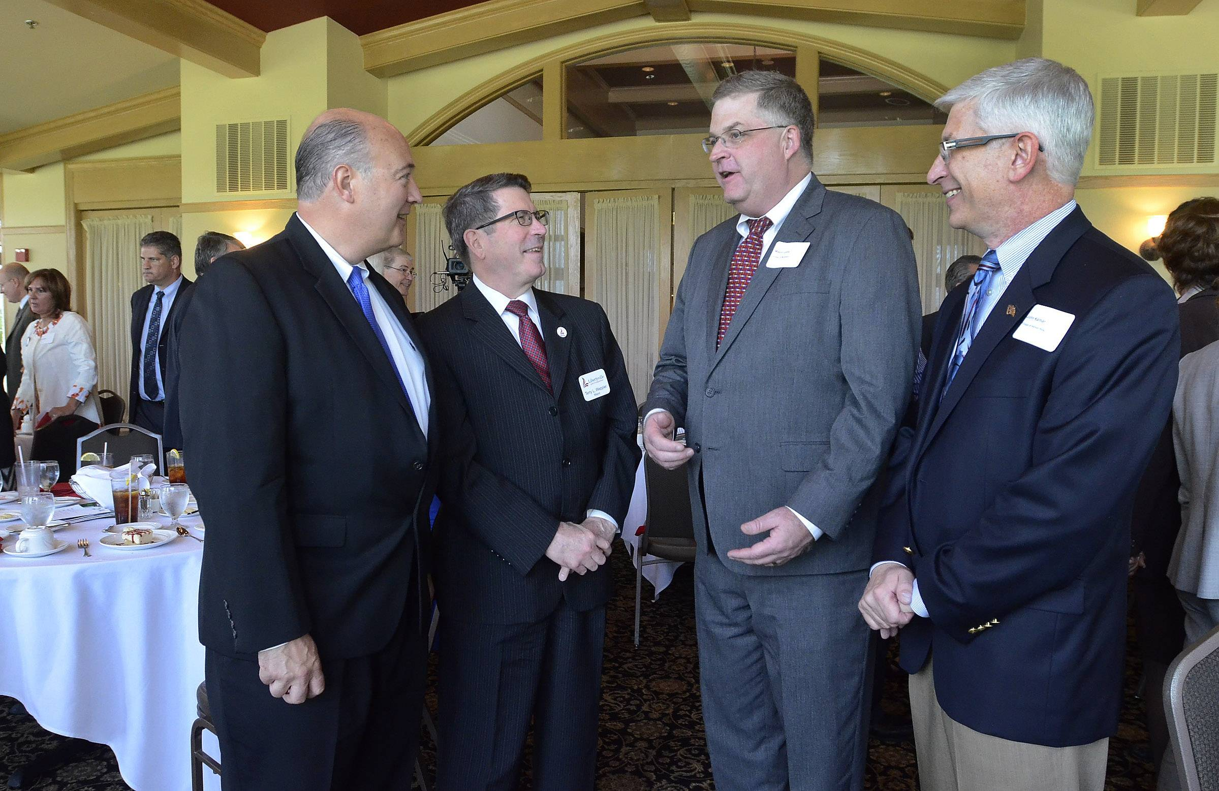 "Green Oaks Trustee John Wagener, left, Libertyville Mayor Terry Weppler, Mundelein Mayor Steve Lentz and Vernon Hills Village Manager John Kalmar chat after Tuesday's 2014 GLMV ""Ask the Mayors"" luncheon at White Deer Run Golf Course in Vernon Hills. More than 85 people attended the gathering."