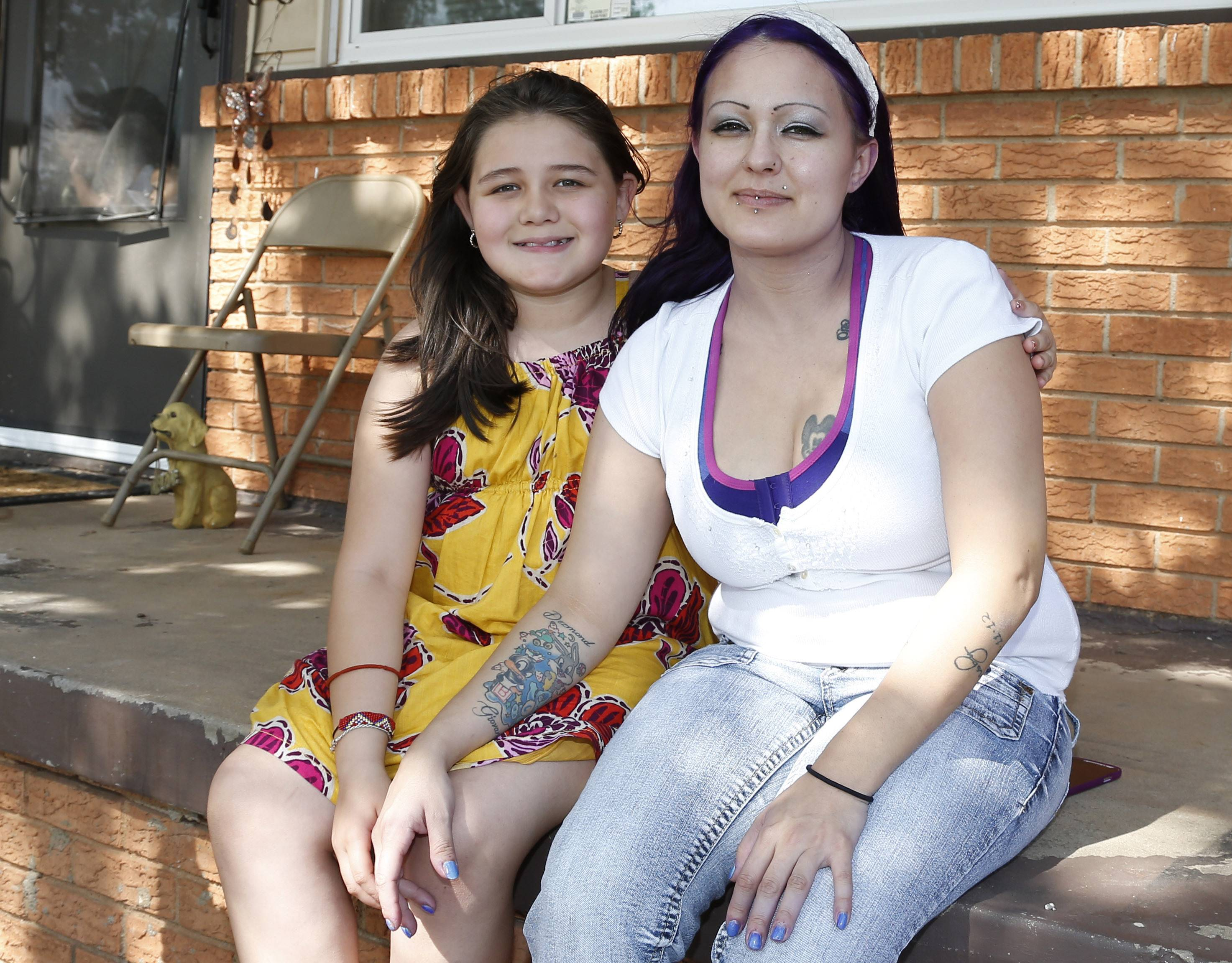LaTisha Garcia, right, with her daughter, Jazmin Rodriguez, left, in front of their new home in Oklahoma City. After the May 20, 2013, tornado trapped Jazmin in debris at Plaza Towers Elementary school and destroyed their home, Garcia did not want to return to live in Moore., Okla.