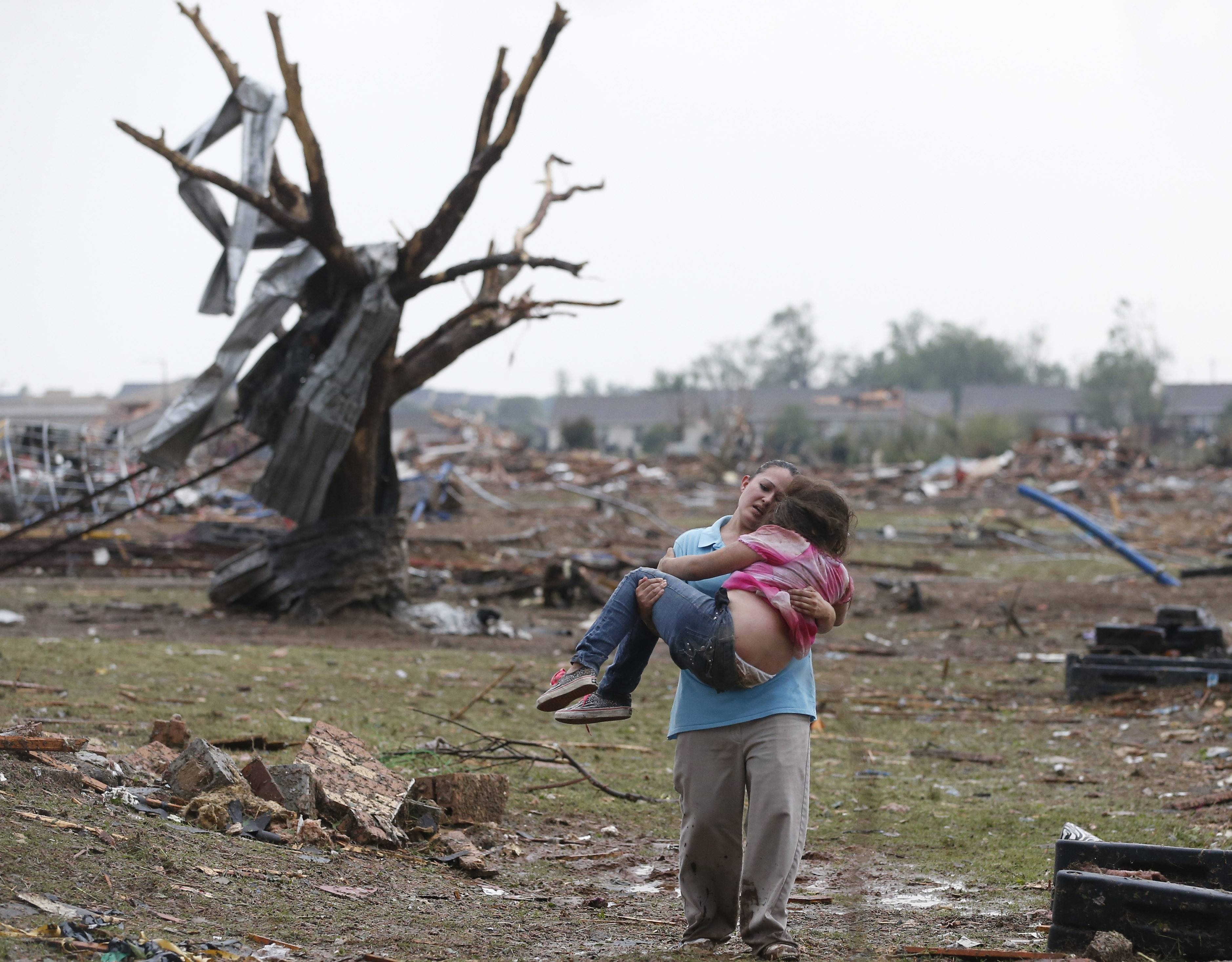 In this May 20, 2013 file photo, LaTisha Garcia carries her daughter, Jazmin Rodriguez, through a field near the collapsed Plaza Towers Elementary School in Moore, Okla. Jazmin was a third grade student at Plaza Towers Elementary school, where the tornado destroyed the school, trapping third grade students under rubble. Seven students died.